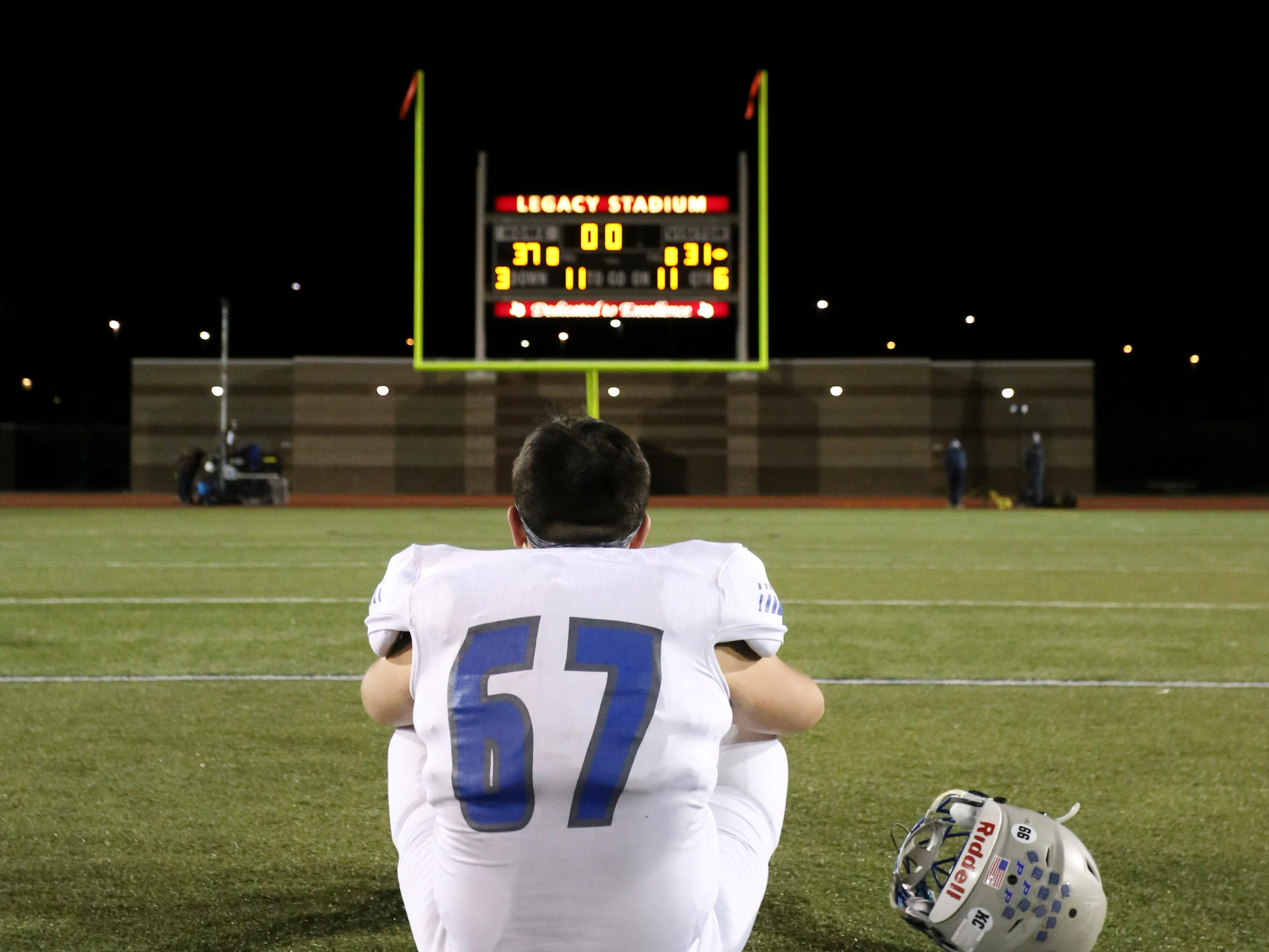 Poudre High School's Cole Bay sits on the field after his team was defeated by Cherokee Trail High School on Friday evening in Aurora.