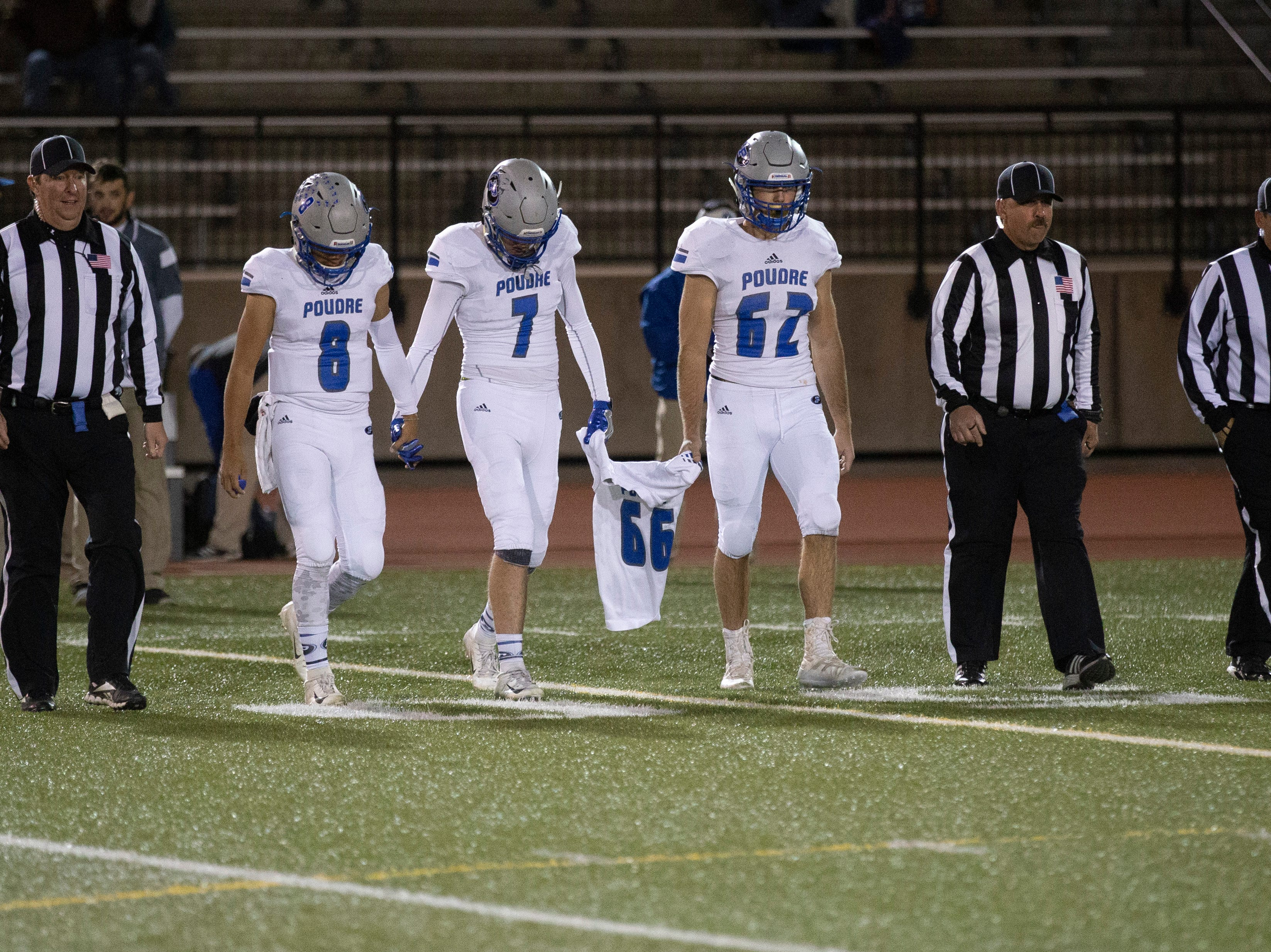 Captains for Poudre High School walk out before the cointoss in an opening round playoff game against Cherokee Trail High School on Friday evening. They're carrying the jersey of Josh Cortez, a Poudre football player who died in a car crash before Poudre's first-round playoff game in 2017.
