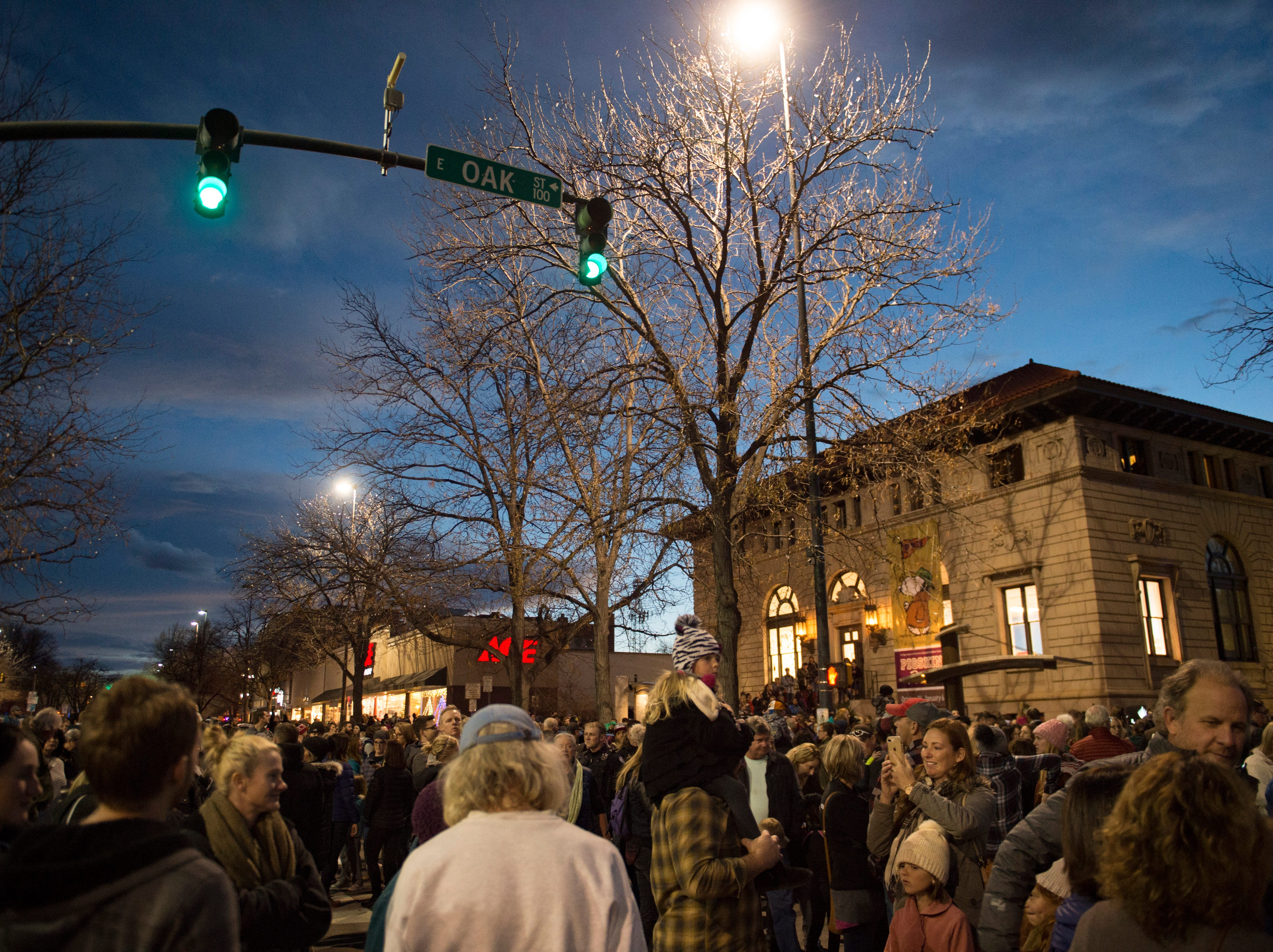 People walk down College Avenue before the holiday lights are turned on in Old Town on Friday, November 2, 2018. College Avenue was closed for public safety during the lighting celebration.