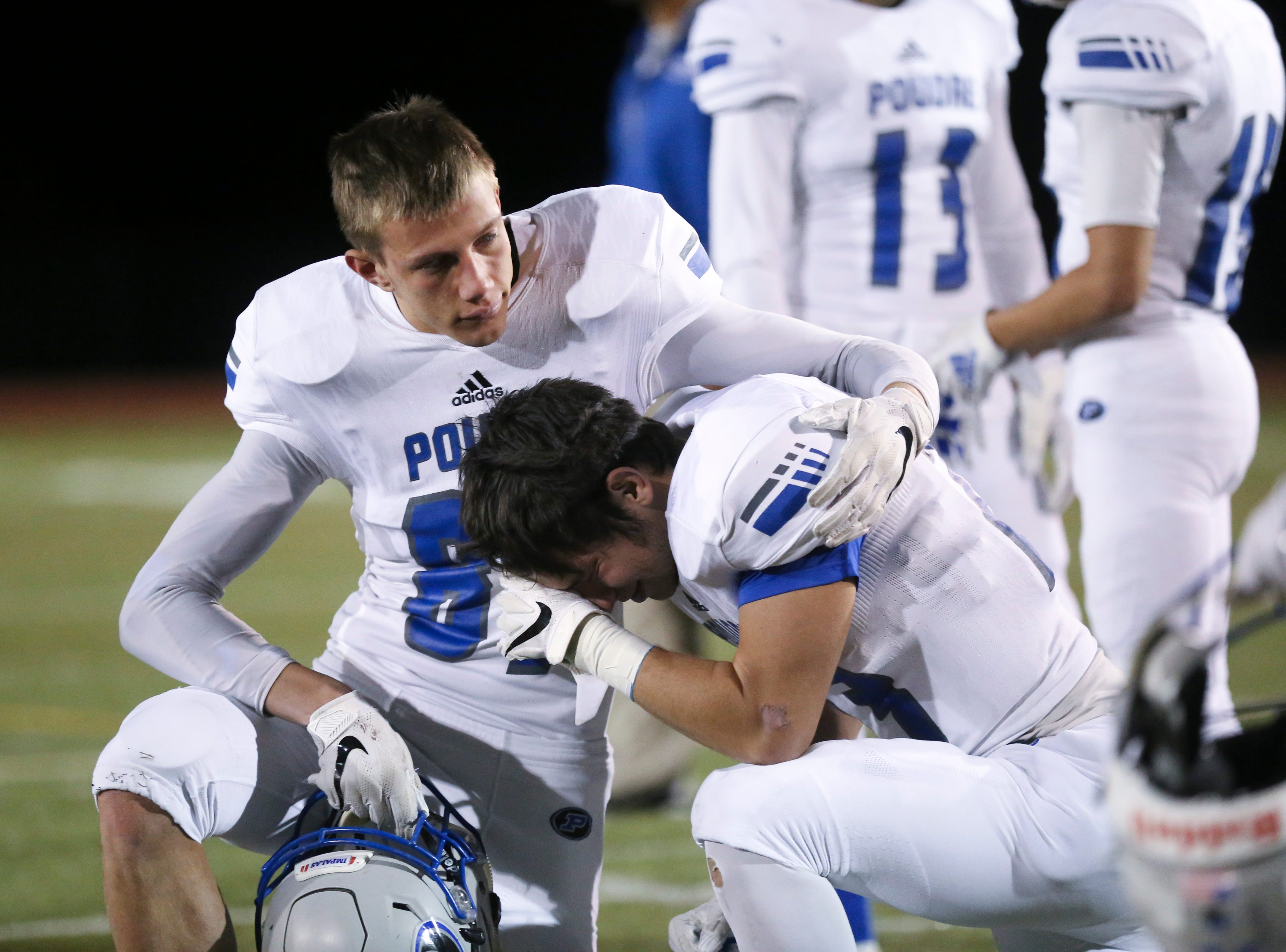 Poudre High School players console each other after being defeated by Cherokee Trail High School in a double overtime playoff game on Friday evening.