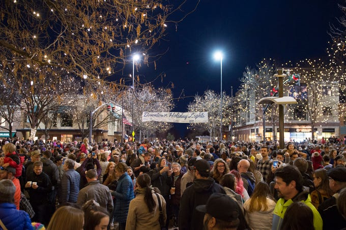 People crowd Oak Street Plaza under the holiday lights in Old Town on Friday, November 2, 2018. The lights will illuminate Old Town until Feb. 14.