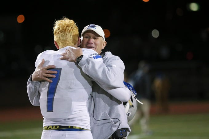 Poudre High School's Josiah Stribling hugs his head coach, Marty McVicker, after being defeated by Cherokee Trail High School in a double overtime playoff game on Friday evening.