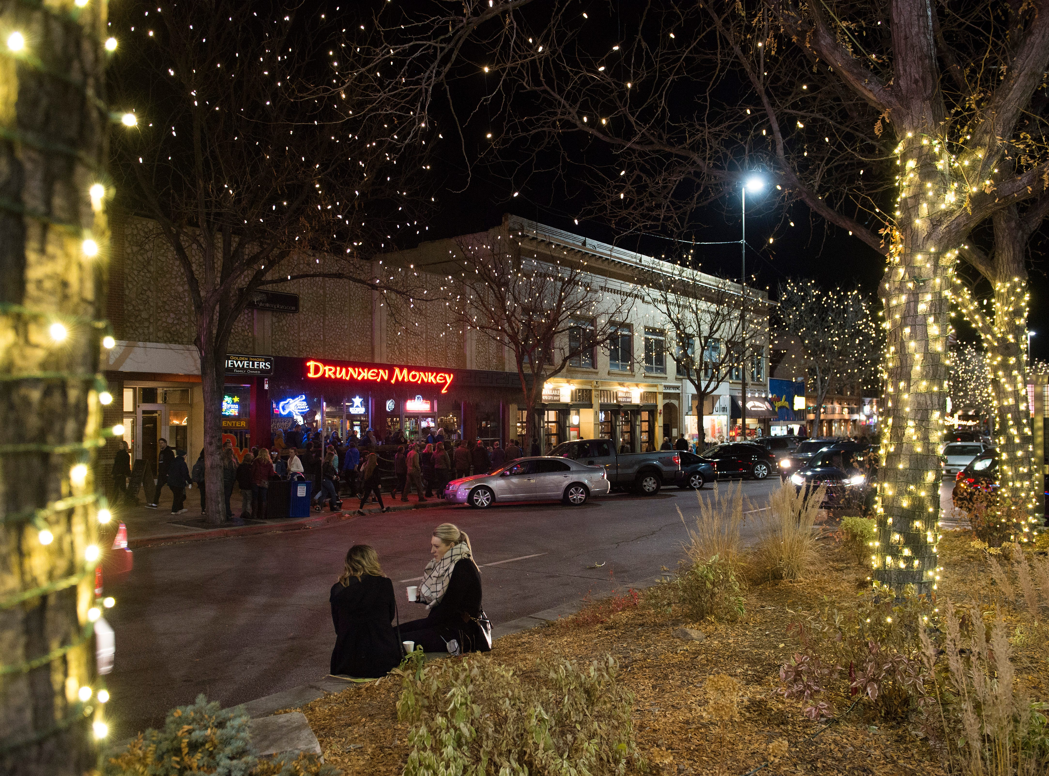 Emma Burns and Megan Sammons sip hot cocoa near College Avenue after the holiday lights are turned on in Old Town on Friday, November 2, 2018. The lights will illuminate Old Town until Feb. 14.