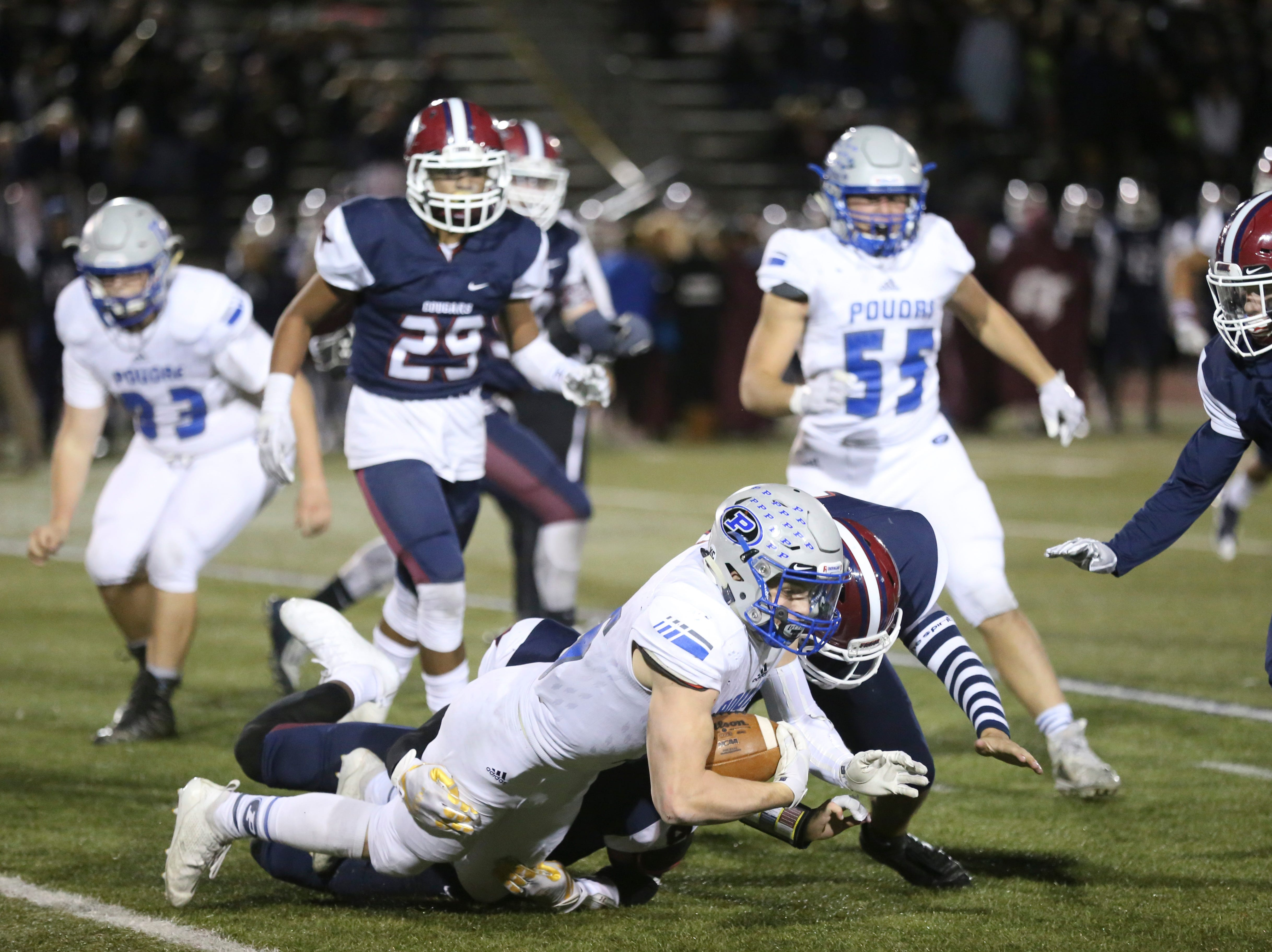 Poudre High School's Tate Satterfield gets tackled by Cherokee Trail High School defenders on Friday evening in Aurora.