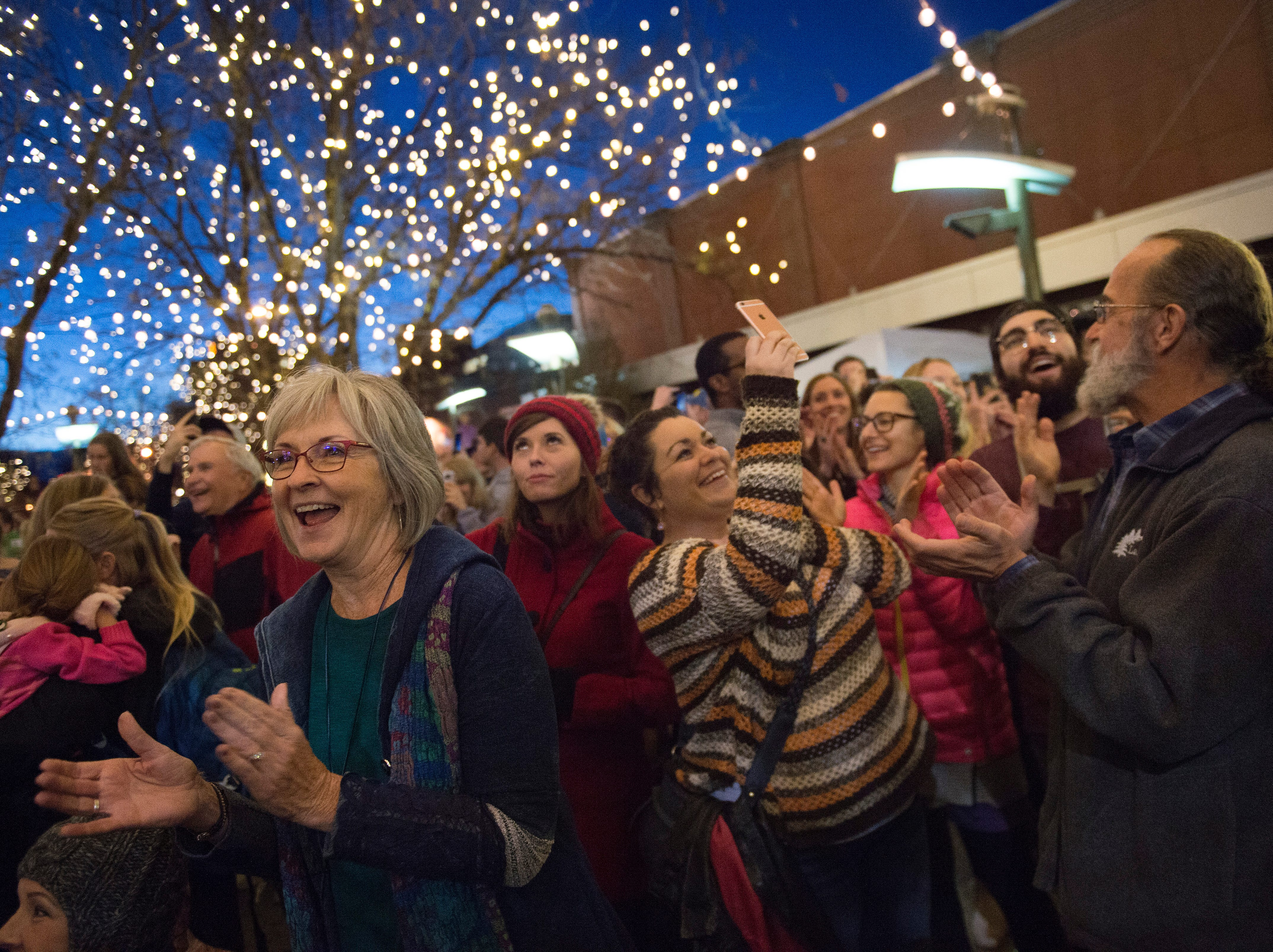 People cheer for the holiday lights after they are turned on in Old Town on Friday, November 2, 2018. The lights will illuminate Old Town until Feb. 14.