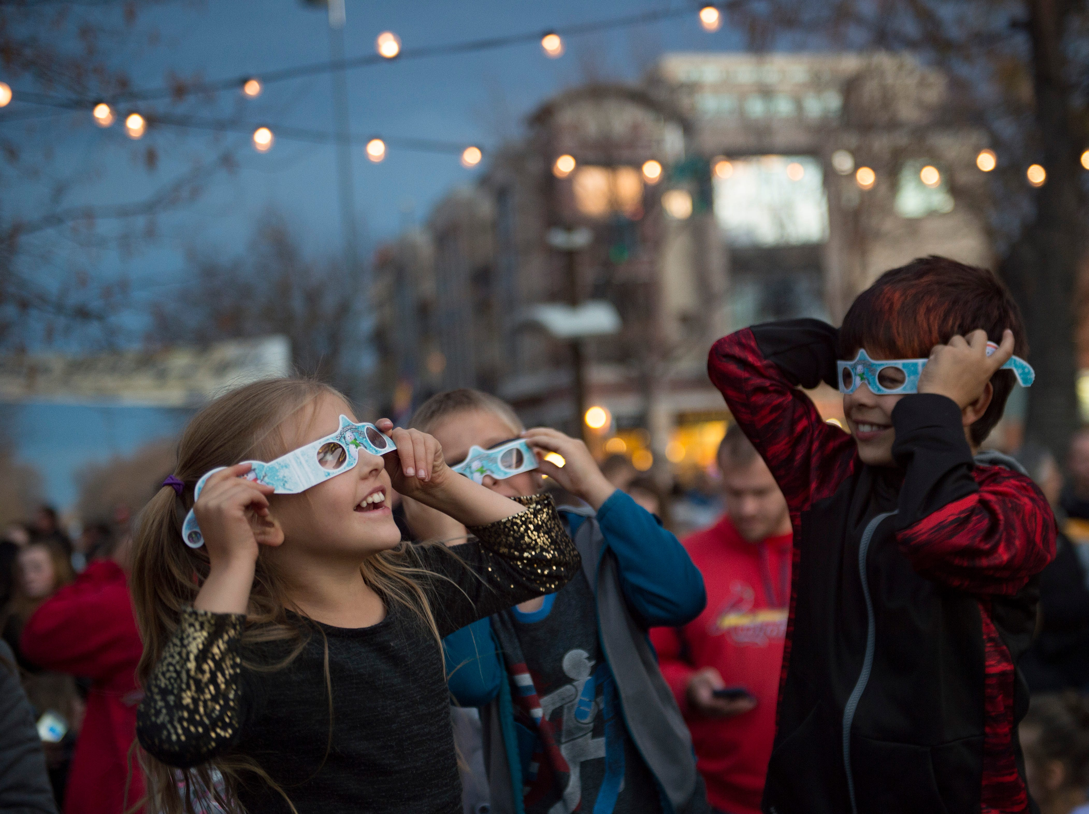 Kids try on their 3D glasses in Oak Street Plaza before the holiday lights are turned on in Old Town on Friday, November 2, 2018. The lights will illuminate Old Town until Feb. 14.
