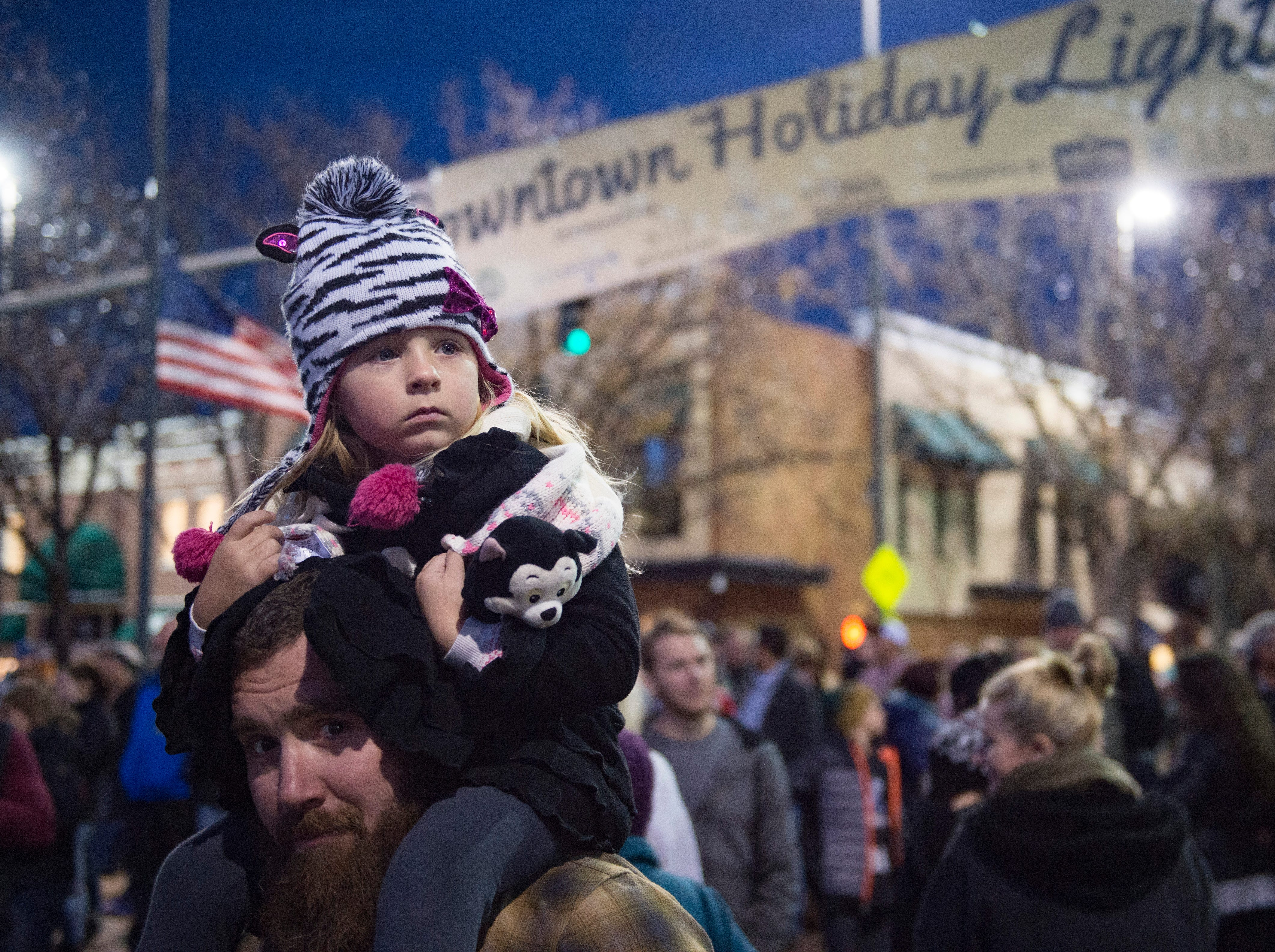 Evie Haring sits on her father, Brian's, shoulders before the holiday lights are turned on in Old Town on Friday, November 2, 2018. The lights will illuminate Old Town until Feb. 14.