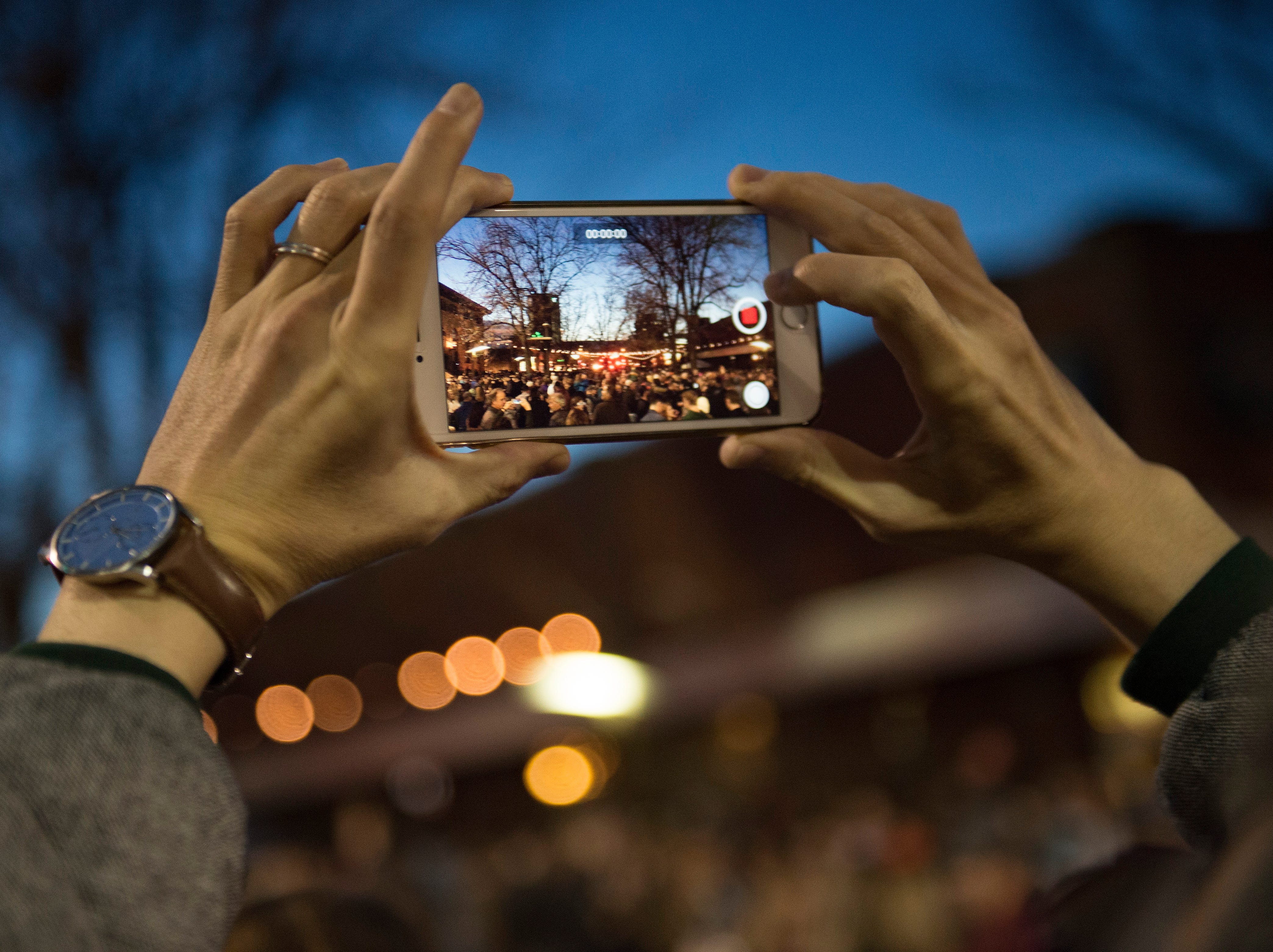 A spectator frames a video before the holiday lights turn on in Oak Street Plaza on Friday, November 2, 2018. The lights will illuminate Old Town until Feb. 14.