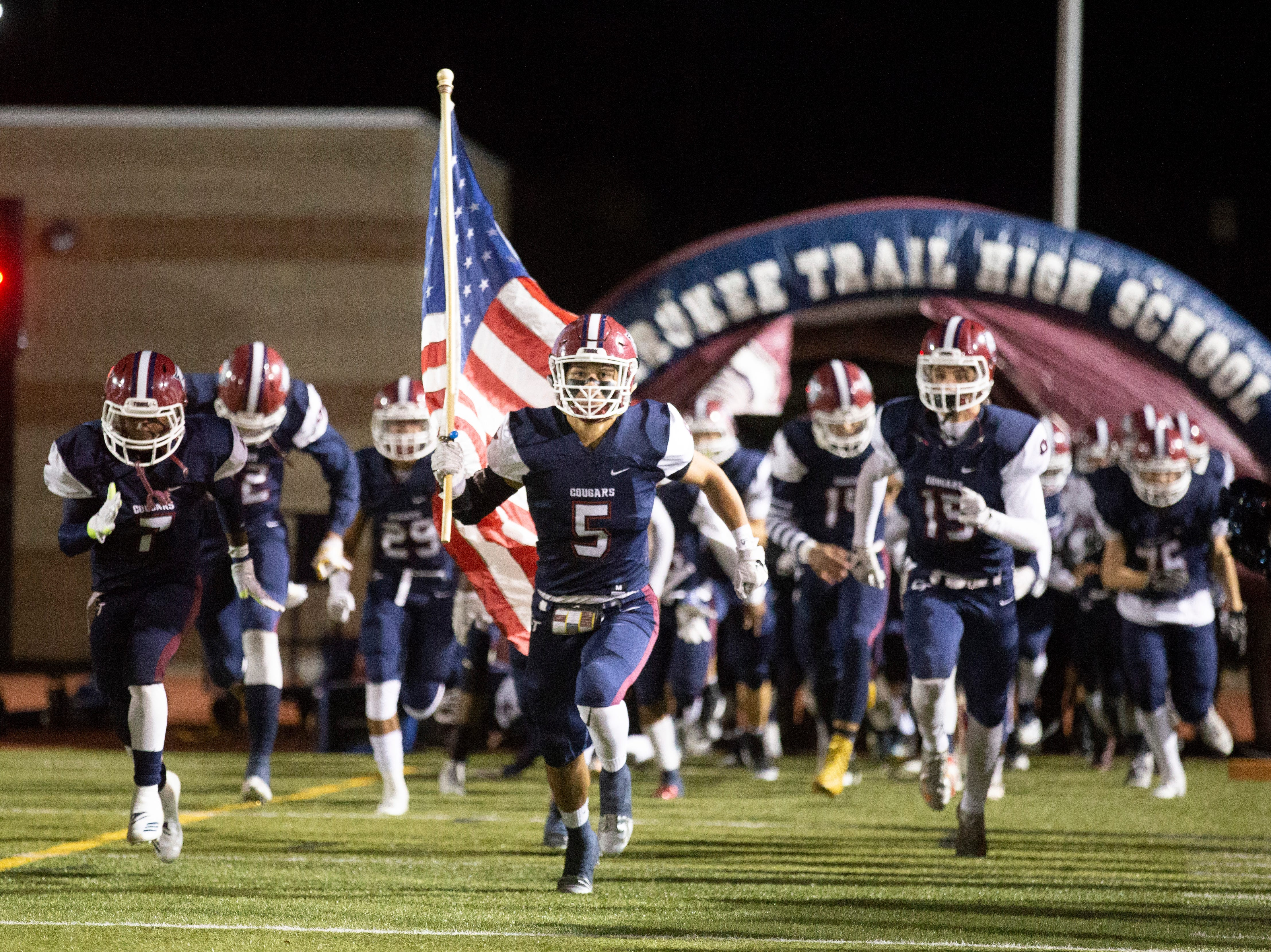Members of the Cherokee Trail High School football team run out of a tunnel before the start of a CHSAA playoff game against Poudre High School on Friday evening in Aurora.