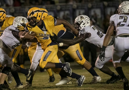 James Chaney of Lehigh is grabbed by Derick Sapp of Riverdale as he runs the ball in a game last year.