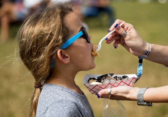 Kassidie Harkenrider takes a bite of Oreo doughnuts from Coasting Donuts during an event in Fort Myers.