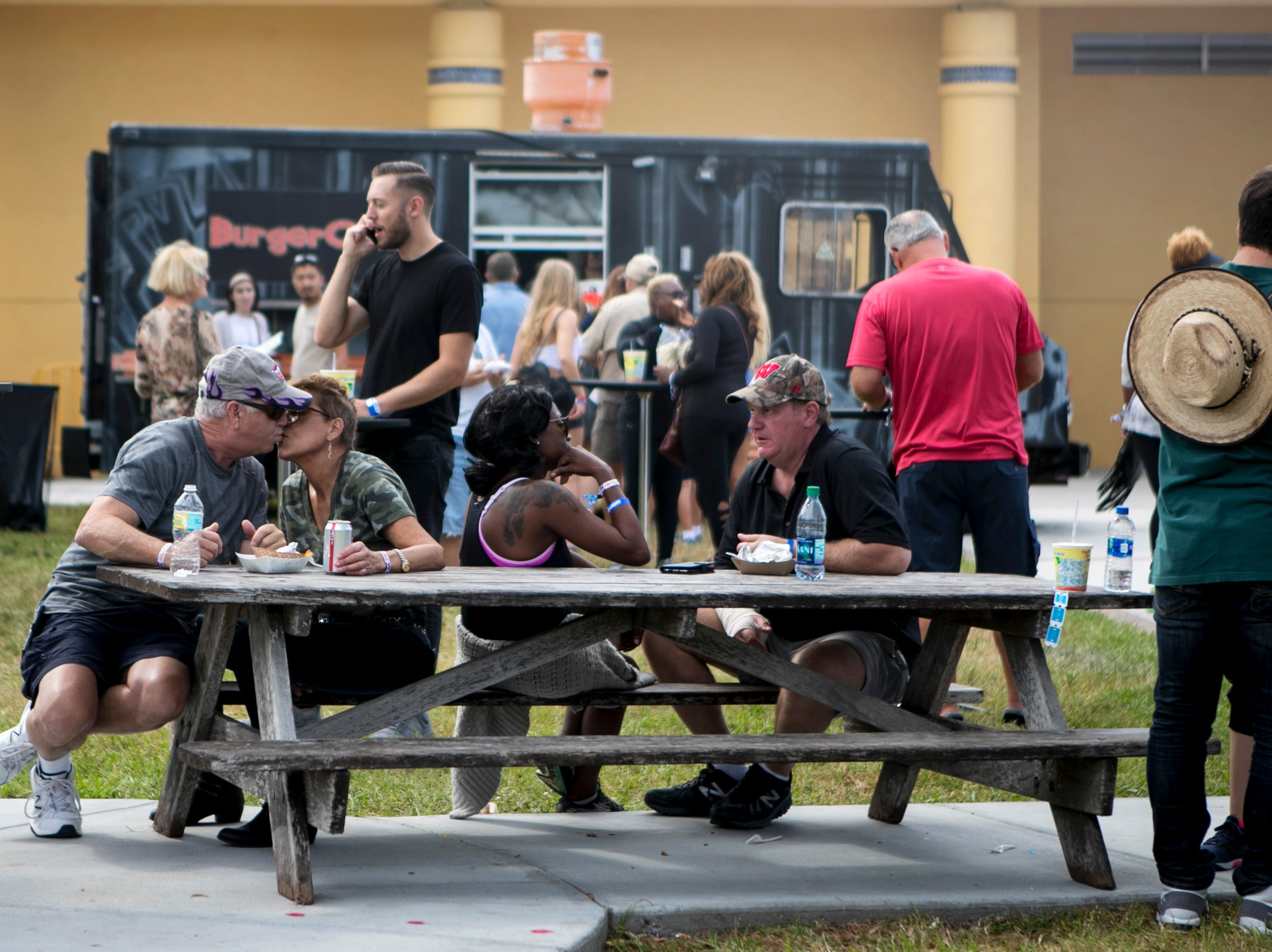 Davia and Donna Cook of Fort Myers, left, share a kiss after eating baklava at Taste of Lee Saturday afternoon at Centennial Park in Fort Myers.