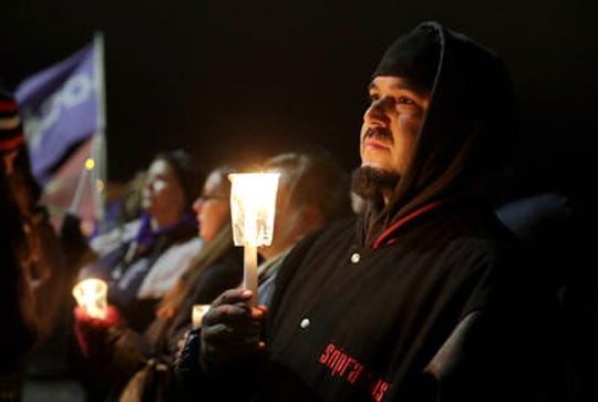 "Cisco Jimenez of Little Chute holds a candle during the ""Justice for Jonathon Rally"" Friday night in downtown Green Bay. The event was organized by Black Lives United-Green Bay and Native Lives Matter after the death of Jonathon Tubby, who was killed by a Green Bay police officer on Oct. 19, 2018."