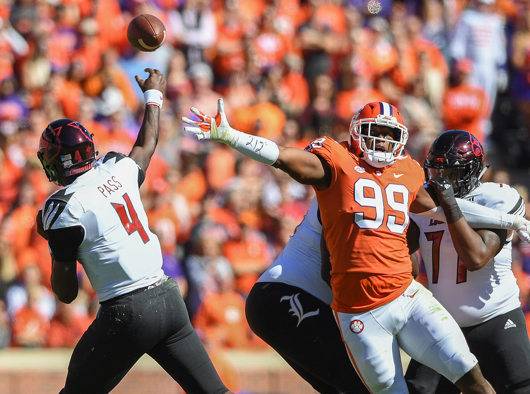 Clemson defensive lineman Clelin Ferrell (99) is held by Louisville offensive lineman Linwood Foy (77) while trying to get to quarterback Jawon Pass (4) during the 1st quarter Saturday, November 3, 2018 at Clemson's Memorial Stadium.