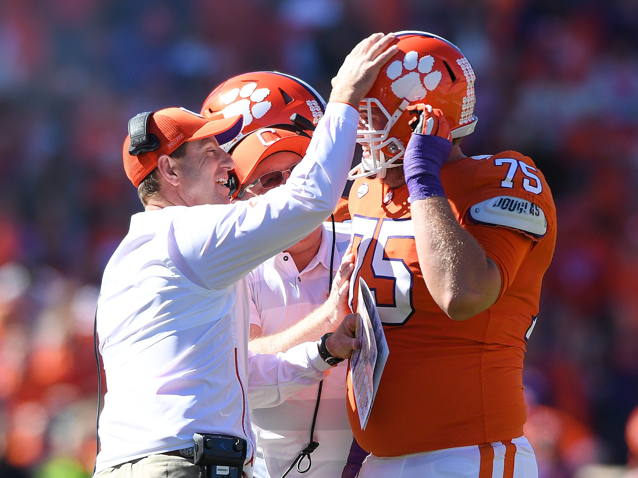 Clemson offensive lineman Mitch Hyatt (75) is congratulated by offensive line coach Robbie Caldwell, center, and head coach Dabo Swinney after breaking the record for most offensive plays by a Clemson player in a carrier during the 2nd quarter against Louisville Saturday, November 3, 2018 at Clemson's Memorial Stadium.