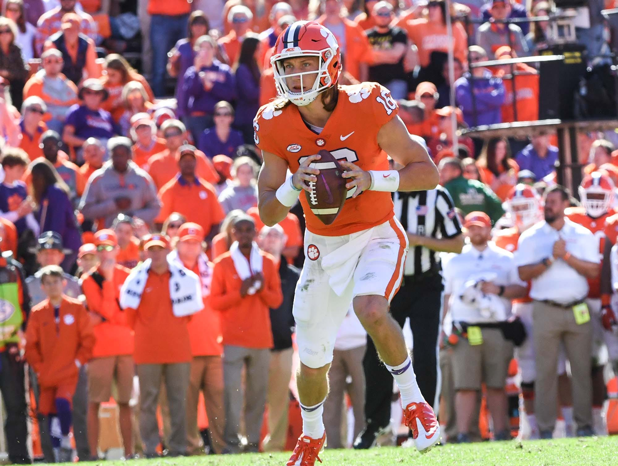 Clemson quarterback Trevor Lawrence (16) rolls out to throw to wide receiver Amari Rodgers (3) for a touchdown during the second quarter in Memorial Stadium on Saturday, November 3, 2018.