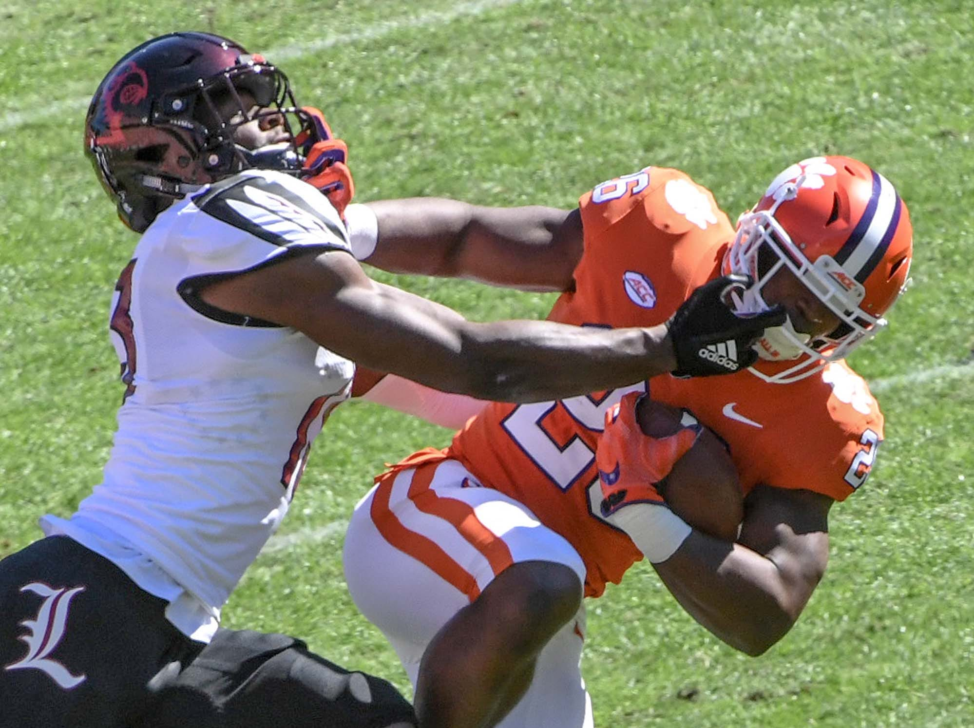 Louisville cornerback Marlon Character(12) reaches to tackle Clemson running back Adam Choice (26) during the first quarter in Memorial Stadium on Saturday, November 3, 2018.