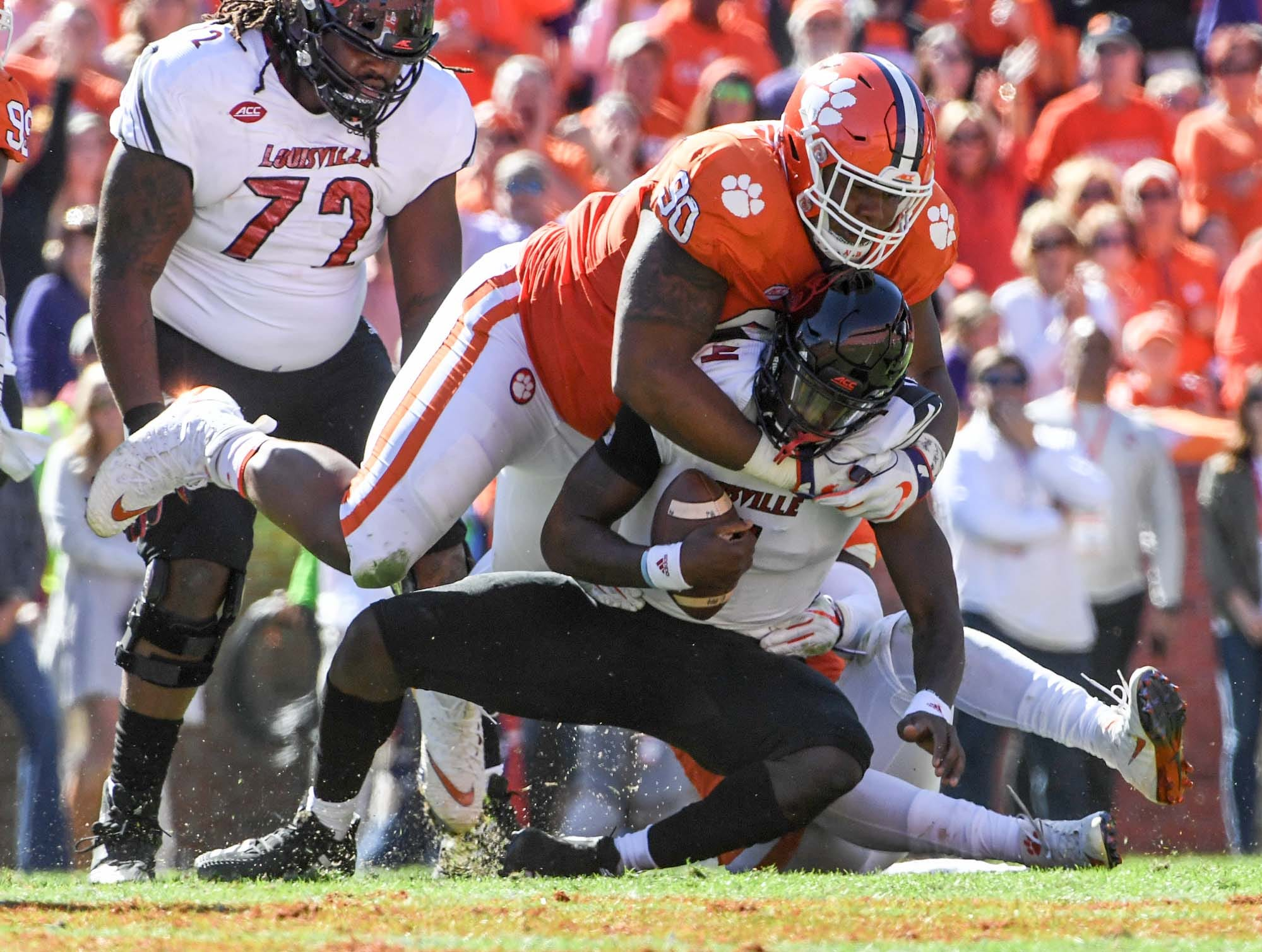 Clemson defensive lineman Dexter Lawrence (90) tackles Louisville quarterback Jawon Pass(4) during the second quarter in Memorial Stadium on Saturday, November 3, 2018.