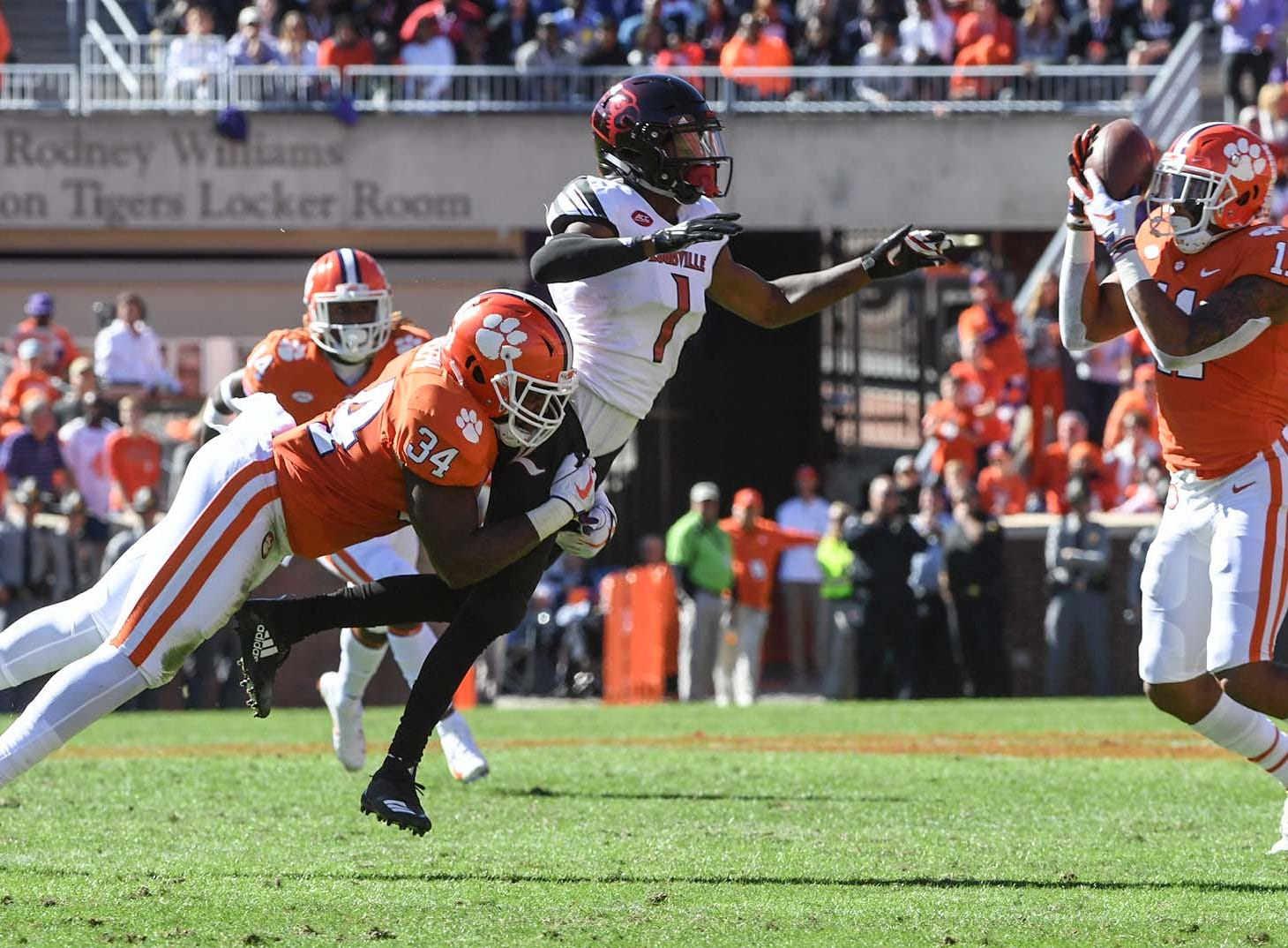 Clemson linebacker Kendall Joseph (34) hits Louisville wide receiver Chatarius Atwell(1) as Clemson safety Isaiah Simmons (11) intercepts the ball and runs it 27-yards for a touchdown during the second quarter in Memorial Stadium on Saturday, November 3, 2018.