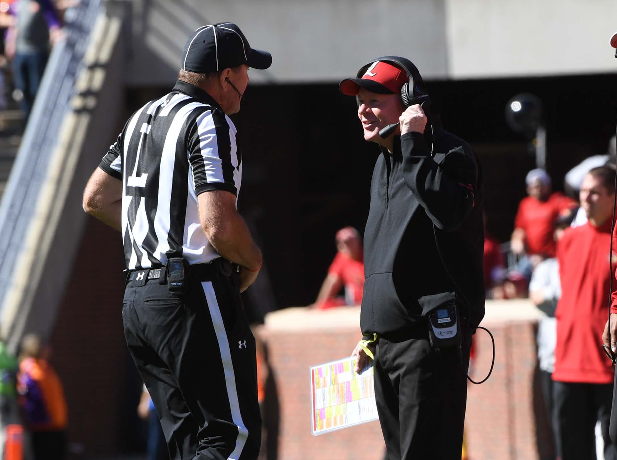 Louisville Head Coach Bobby Petrino talks to a referee during the first quarter in Memorial Stadium on Saturday, November 3, 2018.
