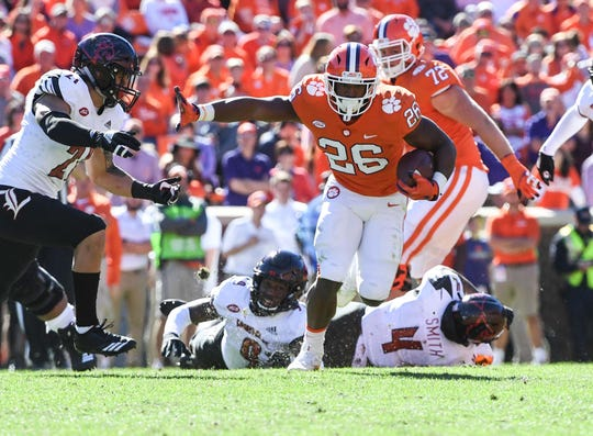 Clemson running back Adam Choice (26) runs by Louisville safety TreSean Smith(4) during the fourth quarter in Memorial Stadium on Saturday, November 3, 2018.