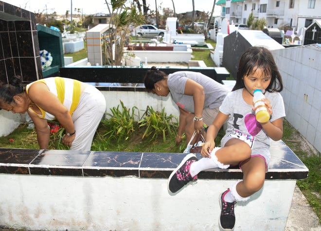 Raeisa Sablan, 7, drinks juice as her mother Melva Duenas, 42, back, and grandmother Mary Naputi, 58, clean a family gravesite at Mount Carmel Cemetery on Saipan on Nov. 2, 2018. The family were visiting gravesites for All Souls' Day.