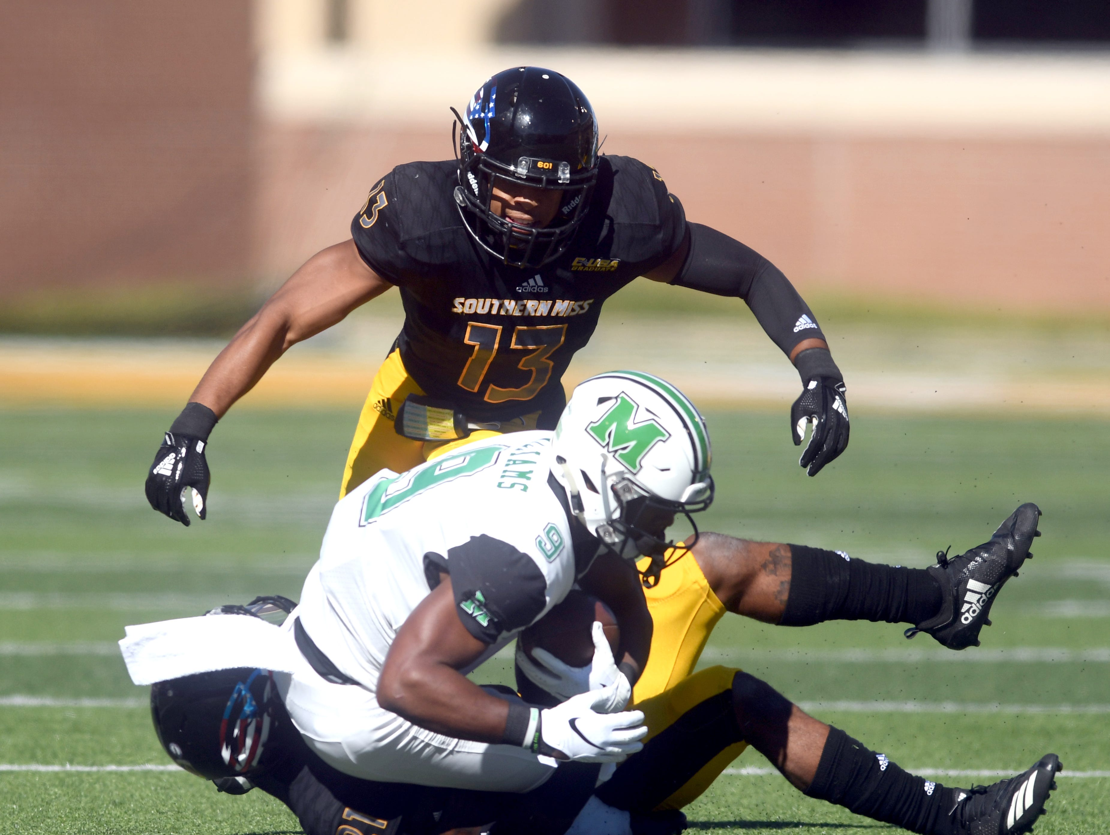 Southern Miss defensive backs Rachuan Mitchell (21) and Picasso Nelson Jr. (13) make a tackle in a game against Marshall at M.M. Roberts Stadium on Saturday, November 3, 2018.