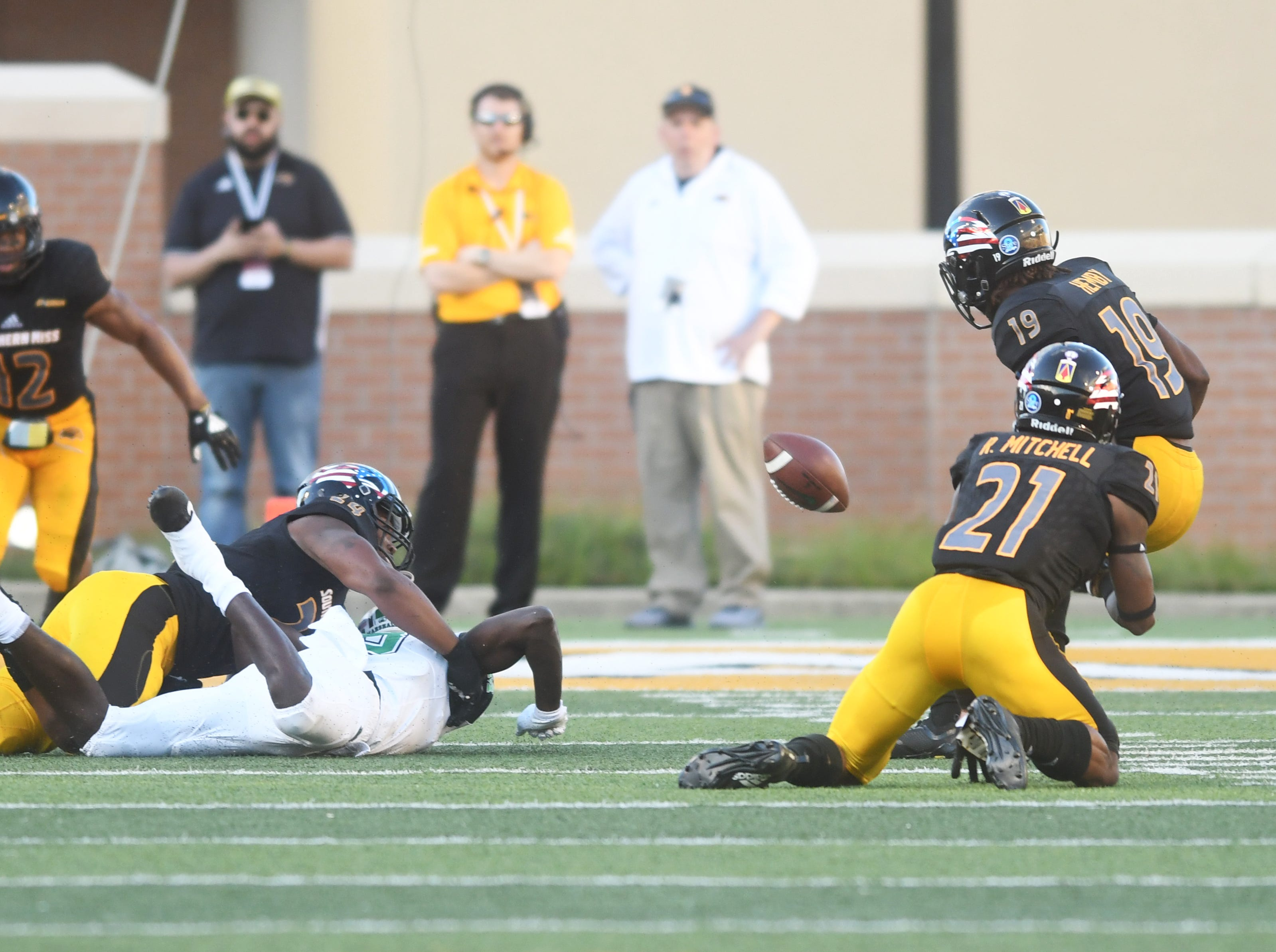 Southern Miss defensive players force a fumble in a game against Marshall at M.M. Roberts Stadium on Saturday, November 3, 2018.