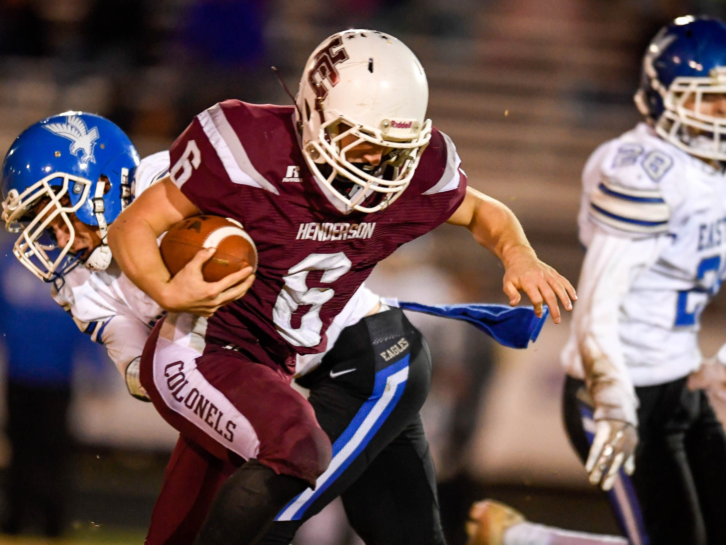 Henderson's Logan Green (6) slips past a tackle from Eastern's Trevor Bieckert (12) as the Henderson County Colonels play the Louisville Eastern Eagles in the first round of the 6-A playoffs at Colonel Field Friday, November 2, 2018.
