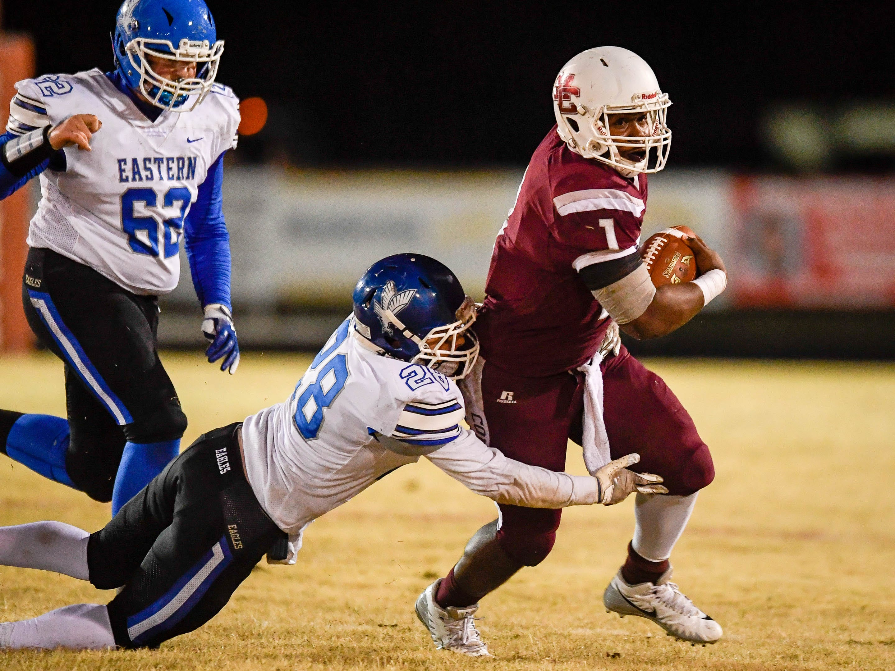 Henderson quarterback Skip Patterson (1) scrambles for extra yards as Eastern's Braden Hafling (28) tries to pull him down as the Henderson County Colonels play the Louisville Eastern Eagles in the first round of the 6-A playoffs at Colonel Field Friday, November 2, 2018.