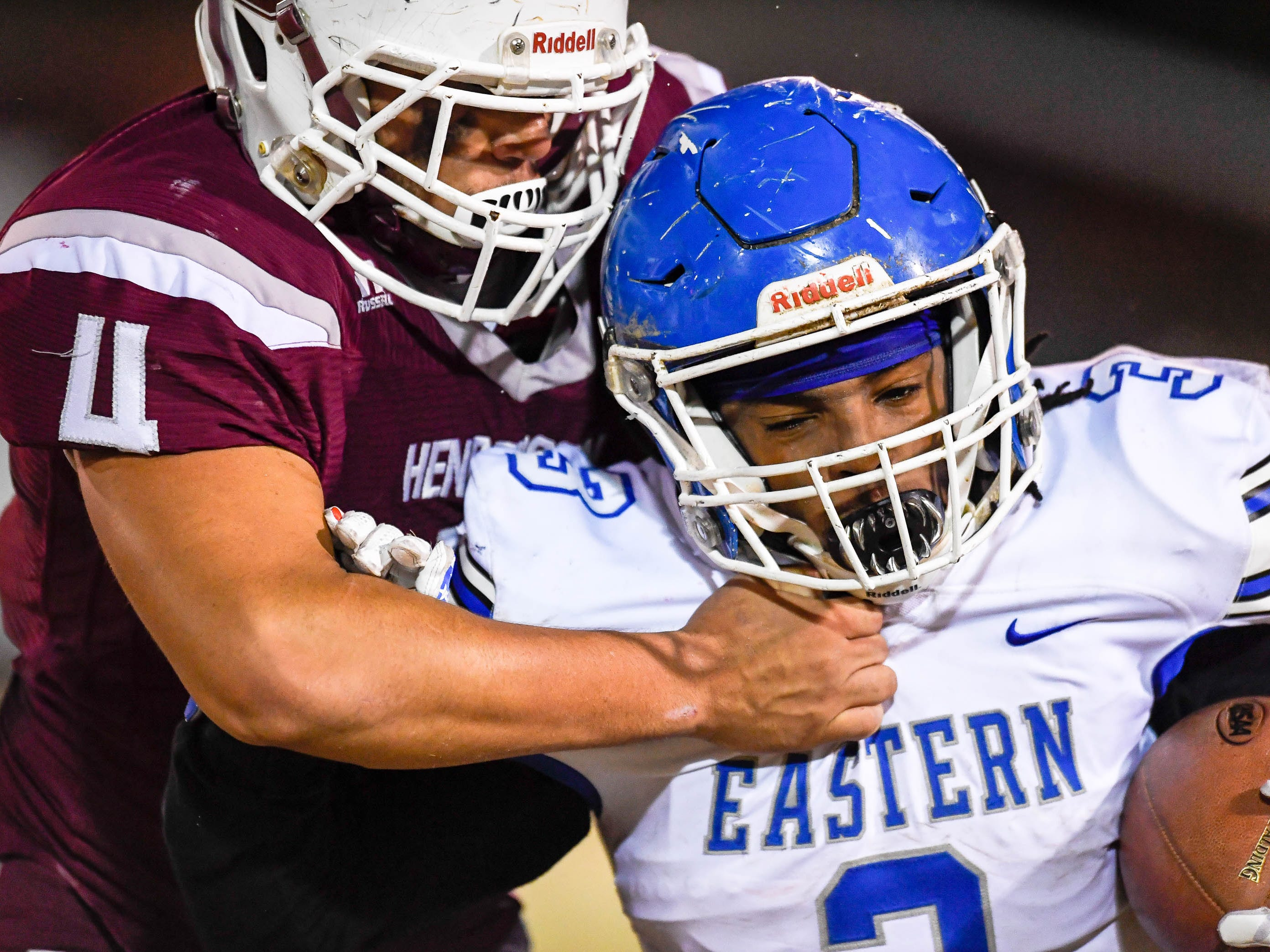 Henderson's Layton Fletcher (4) tackles receiver Eastern's Elijah Irvine (3) as the Henderson County Colonels play the Louisville Eastern Eagles in the first round of the 6-A playoffs at Colonel Field Friday, November 2, 2018.