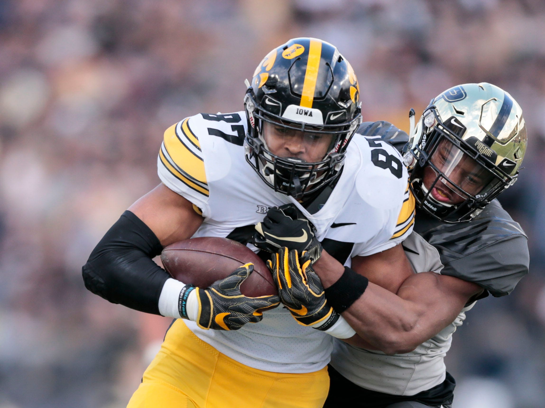 Iowa tight end Noah Fant, left, is tackled by Purdue safety Navon Mosley in the first half of an NCAA college football game in West Lafayette, Ind., Saturday, Nov. 3, 2018.