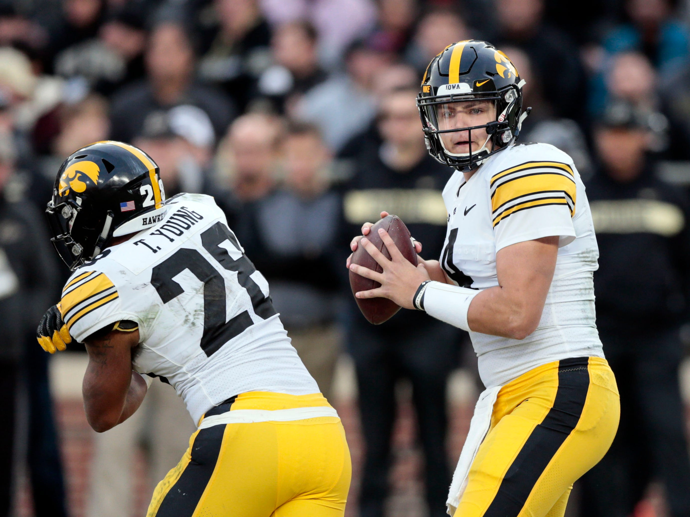 Iowa quarterback Nate Stanley (4) drops back behind running back Toren Young (28) while playing against Purdue in the second half of an NCAA college football game in West Lafayette, Ind., Saturday, Nov. 3, 2018.