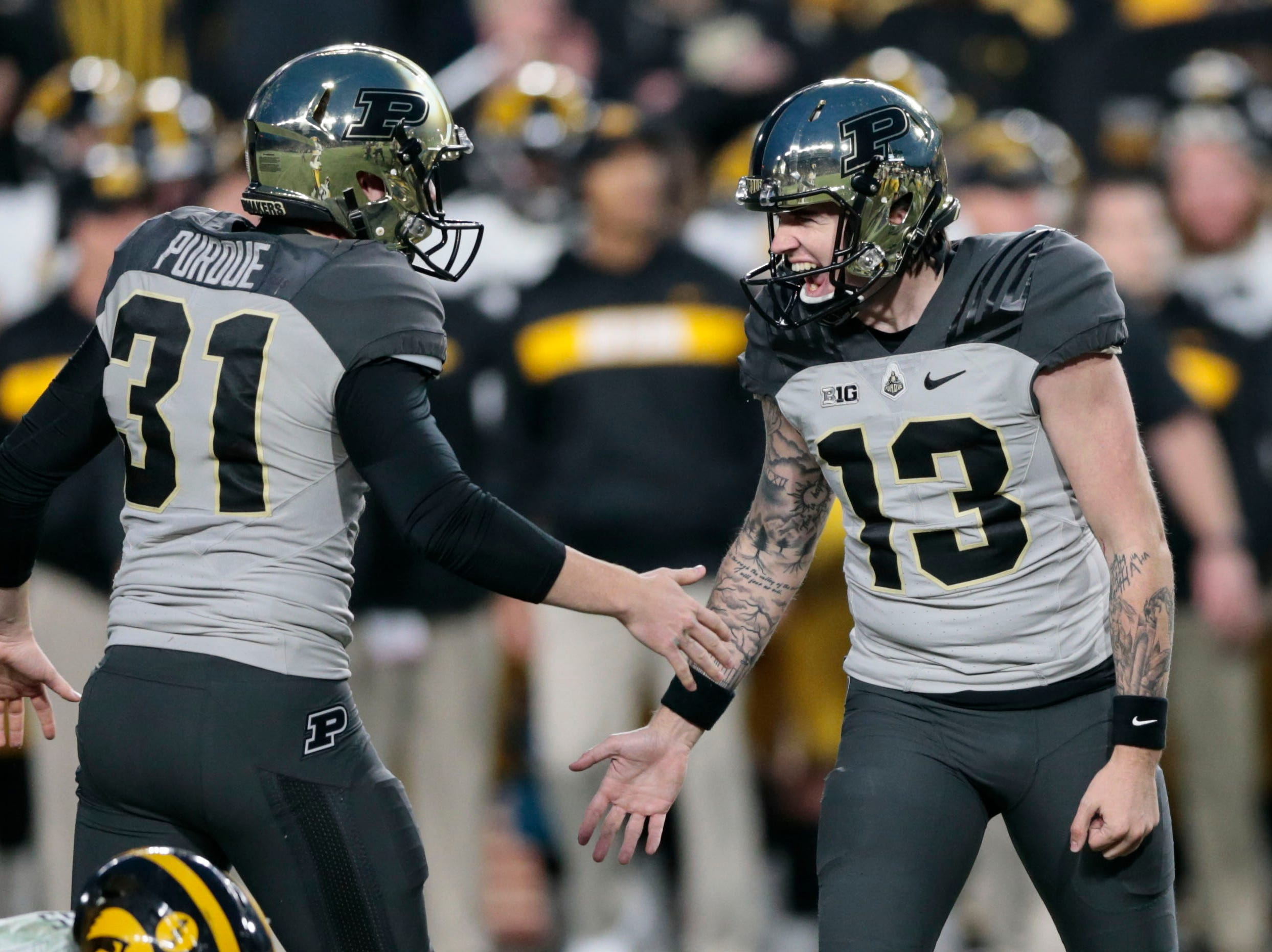 Purdue placekicker Spencer Evans (13) is congratulated by punter Joe Schopper (31) after booting the winning field goal in the fourth quarter of an NCAA college football game against Iowa in West Lafayette, Ind., Saturday, Nov. 3, 2018.