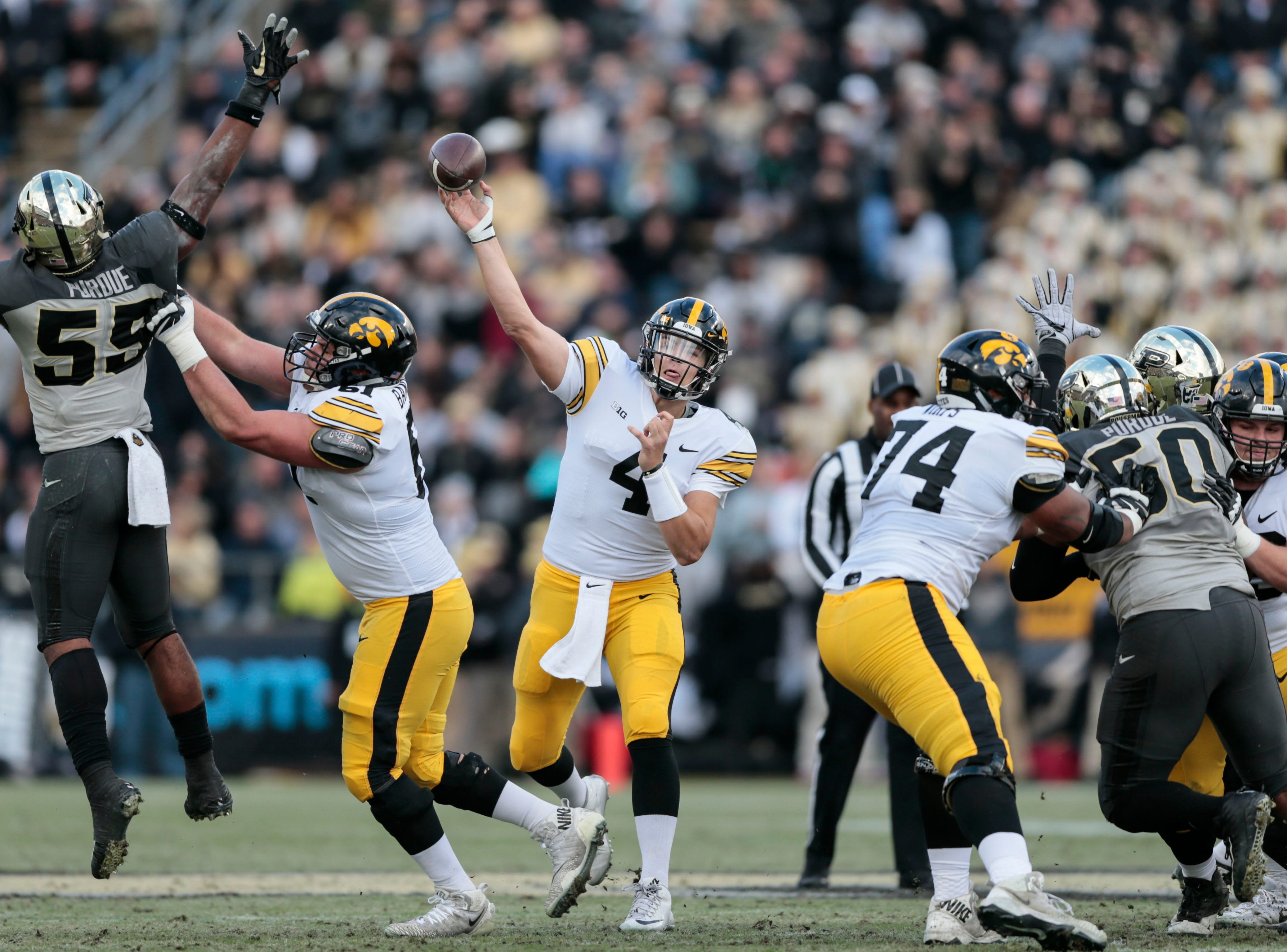 Iowa quarterback Nate Stanley (4) throws a pass as Purdue linebacker Derrick Barnes (55) leaps to defend against it in the first half of an NCAA college football game in West Lafayette, Ind., Saturday, Nov. 3, 2018.