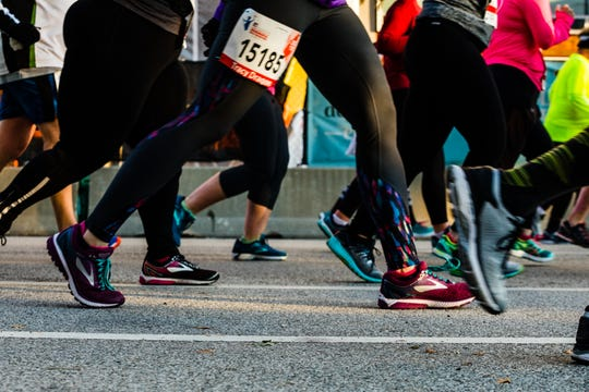 A slew of running shoes pass on a street downtown during the Monumental Marathon.
