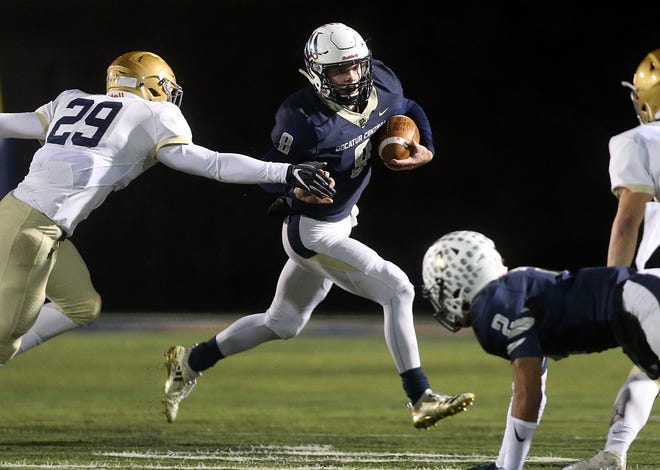 Decatur Central's Parker Harrington (8) runs the ball by Cathedral's inside linebacker Will Goheen (29) in the first half of the sectional final game at Decatur Central High School in Indianapolis, Ind., Saturday, Nov. 2, 2018. The Hawks defeated the Irish 21-14 for the sectional championship title.