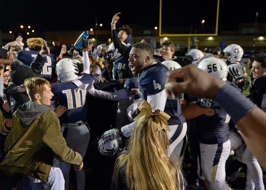 Decatur Central players and fans celebrate their victory against Cathedral in the sectional final game at Decatur Central High School in Indianapolis, Ind., Saturday, Nov. 2, 2018. The Hawks defeated the Irish 21-14 for the sectional championship title.