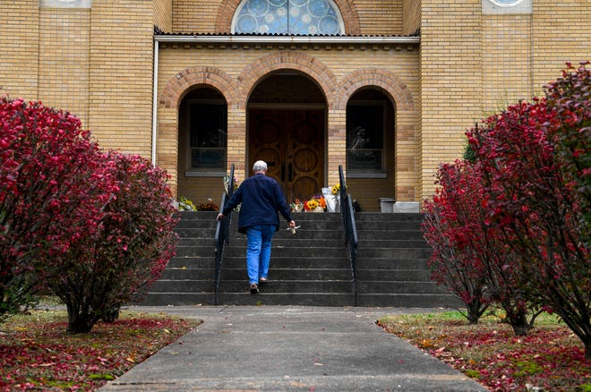 Pastor Pat Parham of Jackson walks up the steps to place his offering of sympathy at the doorstep of Congregation B'nai Israel in Jackson, Tenn., on Friday, Nov. 2, 2018.
