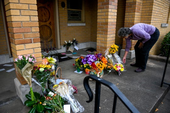 Rebecca Cook drops off an offering of flowers at the doorstep of Congregation B'nai Israel in Jackson, Tenn., on Friday, Nov. 2, 2018.