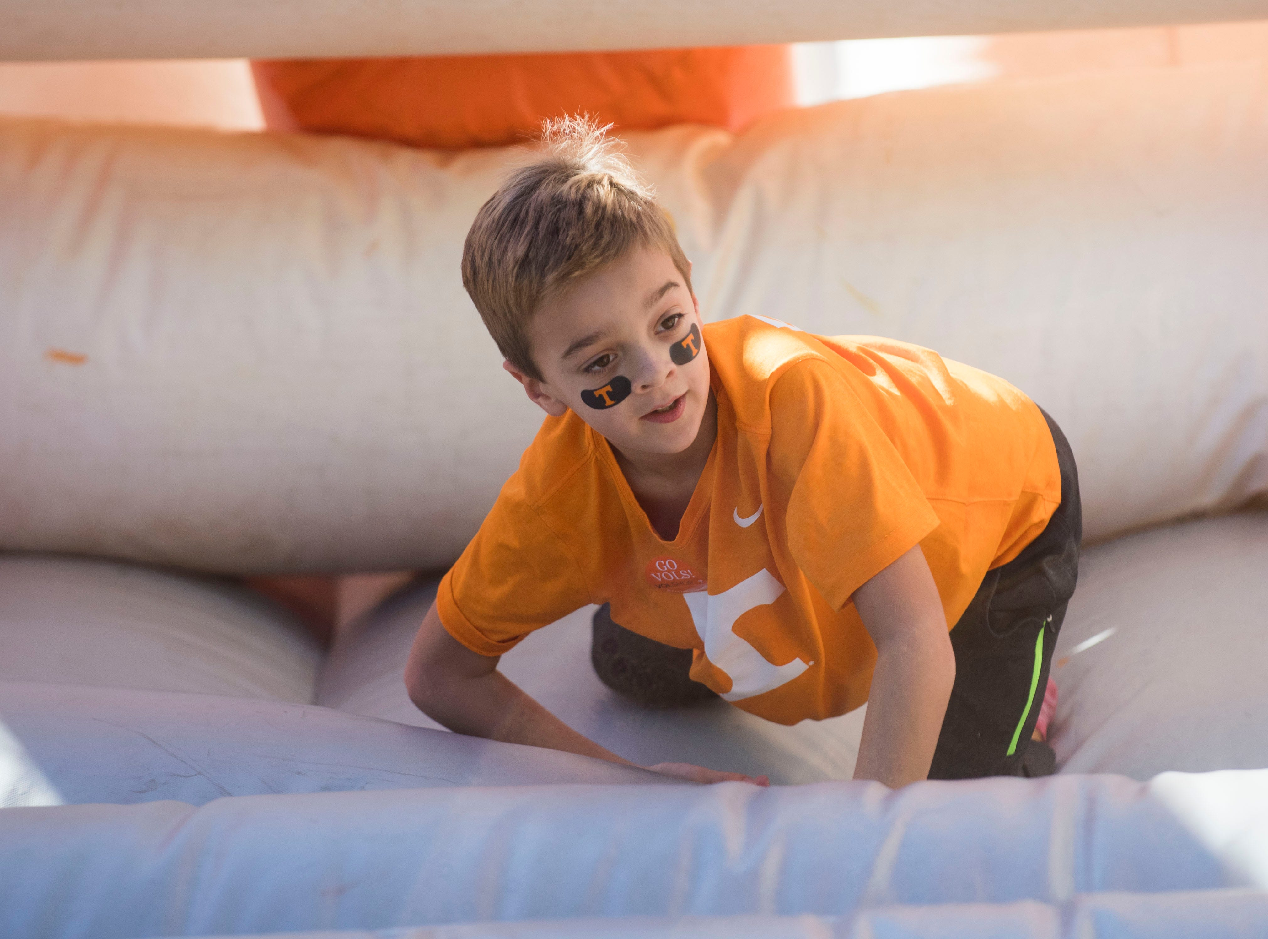 A young Tennessee fan bounces in an inflatable obstacle course before the homecoming game between Tennessee and Charlotte outside of Neyland Stadium Saturday, Nov. 3, 2018.