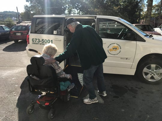 James Malia, a driver with the Volunteer Assisted Transportation program, helps Jill McKenzie in her wheelchair board a van for a trip to a medical appointment. McKenzie relies on VAT for transportation to doctor's appointments and a weekly group where she carves spiral walking sticks with other carvers.