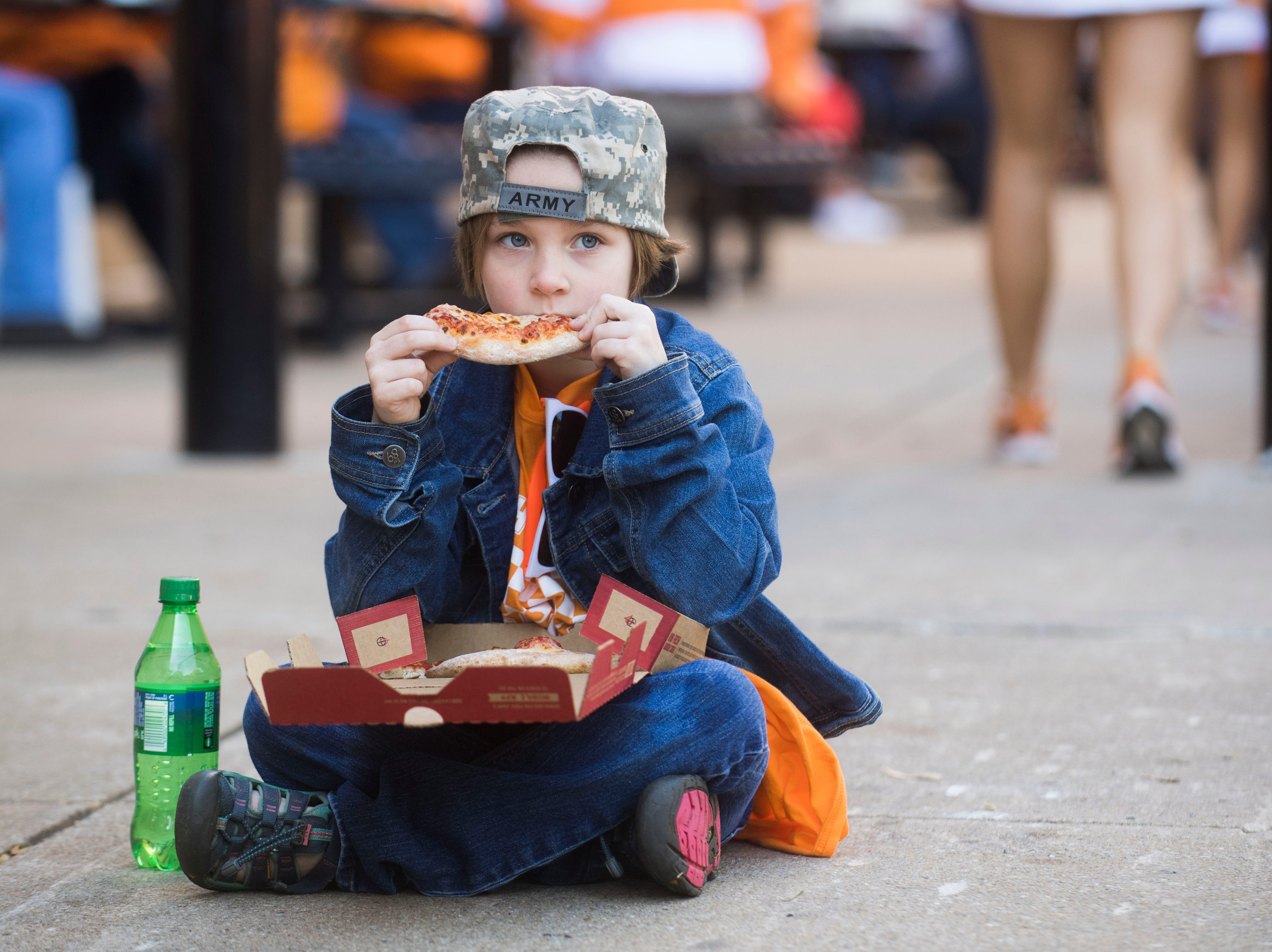 Lauren Puhr, 7, of Knoxville takes a seat while eating pizza before the homecoming game between Tennessee and Charlotte outside of Neyland Stadium Saturday, Nov. 3, 2018.