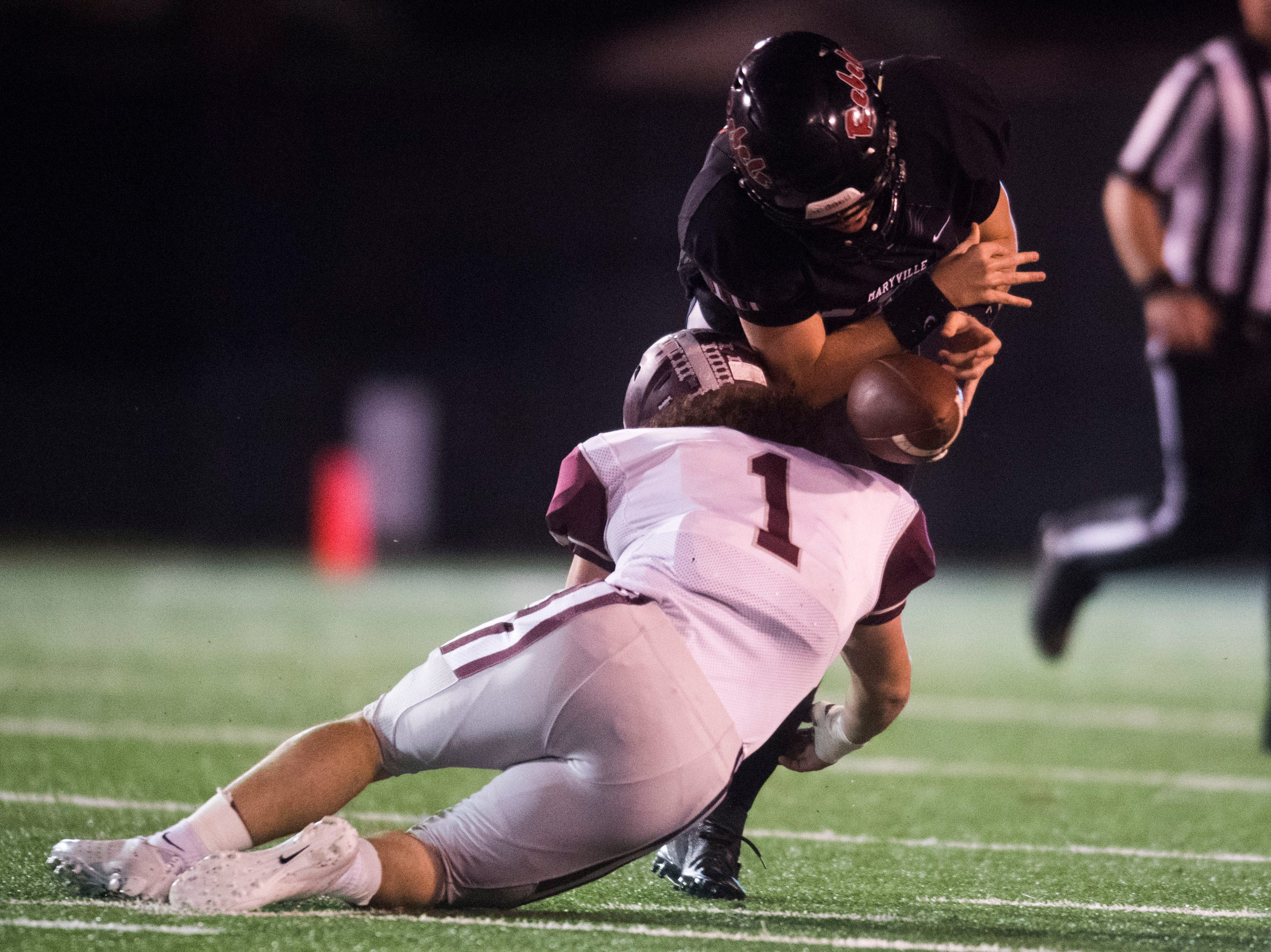 Maryville's Braden Carnes (10) is tackled by Bearden's Caleb Wilkins (1) during a first round playoff game between Maryville and Bearden at Maryville, Friday, Nov. 2, 2018. Maryville defeated Bearden 28-7.