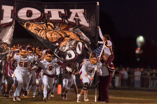 The Iota Bulldogs storm onto the field before their regular-season finale against Eunice on Friday, Nov. 2, 2018.