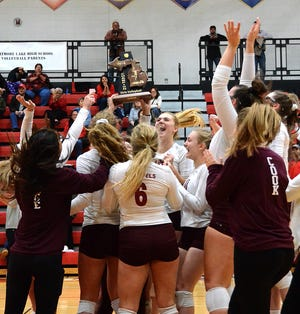 Charyl Stockwell volleyball players hoist the district championship trophy after beating Whitmore Lake on Friday, Nov. 2, 2018.
