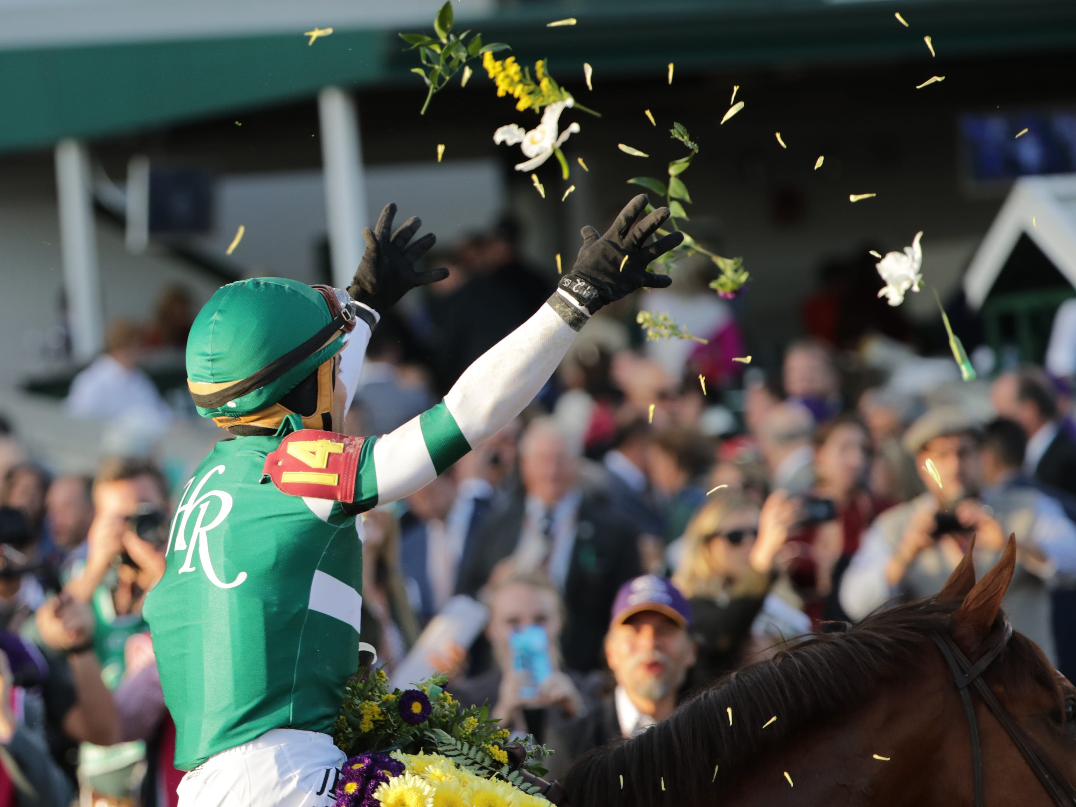 Jockey Joel Rosario tosses flowers in the air after winning the Breeders' Cup Classic aboard Accelerate. Nov. 3, 2018.