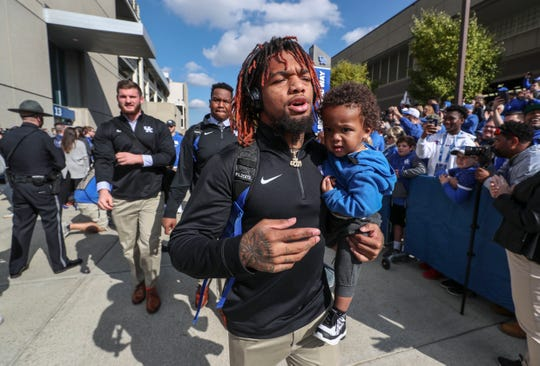Kentucky's Lynn Bowden, Jr. carries his son at the Cat Walk before the Kentucky-Georgia game Saturday. Nov. 3, 2018