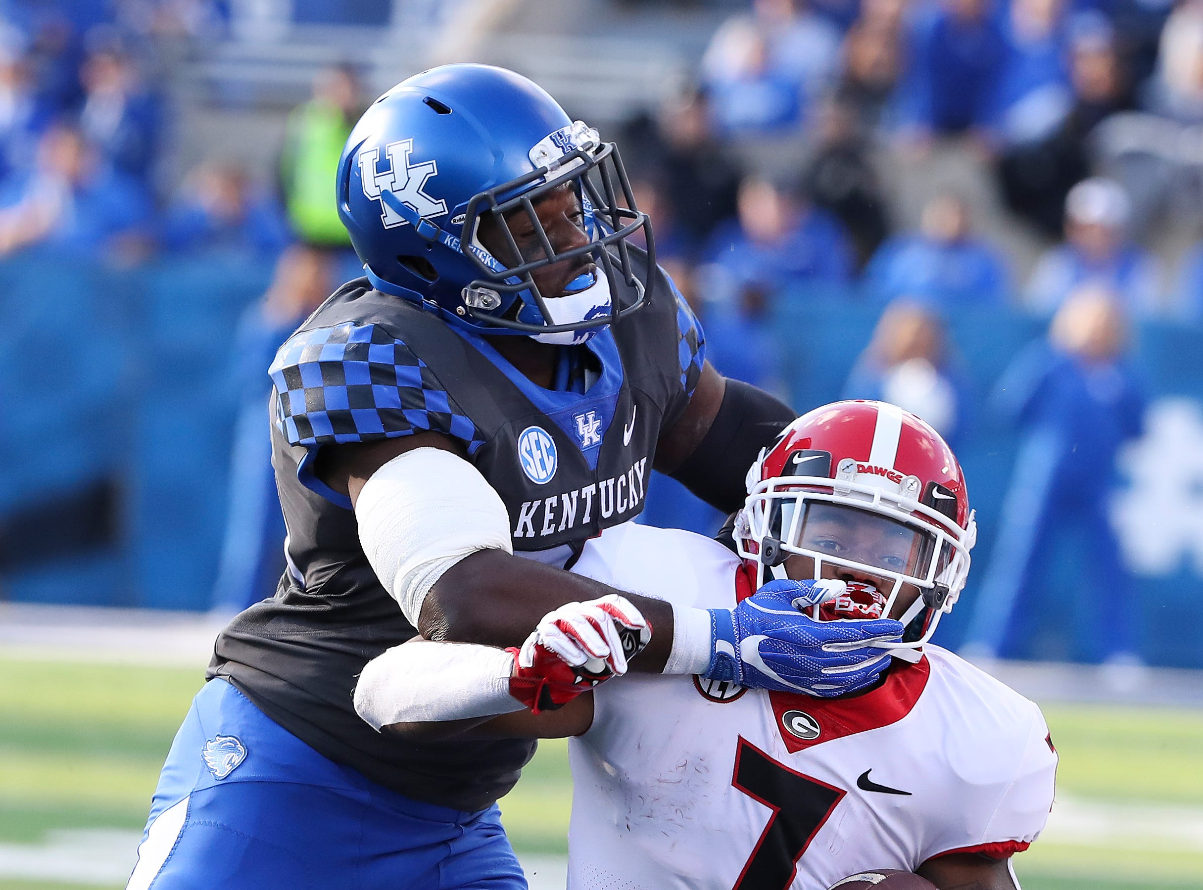 Georgia's D'Andre Swift (7) was brought down by UK's Darius West (25) and a teammate during their game at Kroger Field in Lexington.  