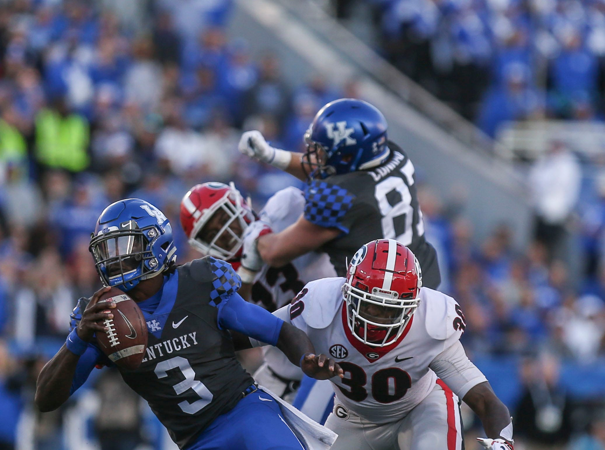 Kentucky's Terry Wilson gets pressured by Georgia's Deangelo Gibbs in the second half as the Bulldogs dogged the Wildcats 34-17 Saturday. Nov. 3, 2018